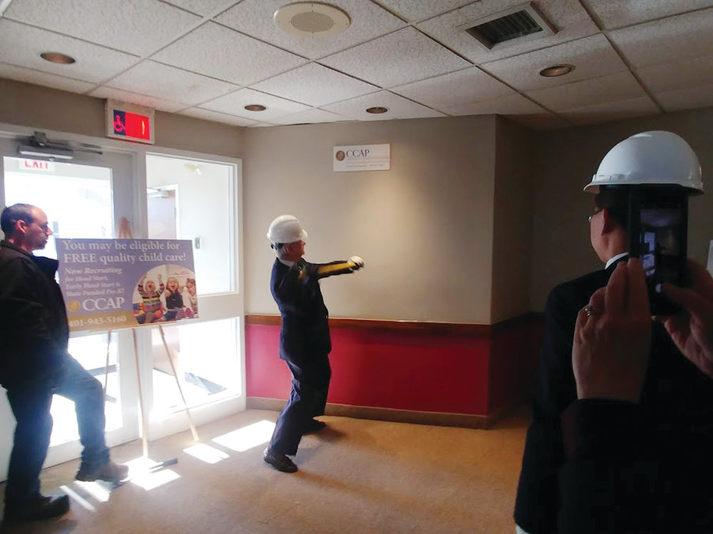 "TAKING THE FIRST SWING: Senator Jack Reed takes the first swing during the ""wall-breaking"" ceremony at the new Early Learning Center location on Broad Street Monday morning."