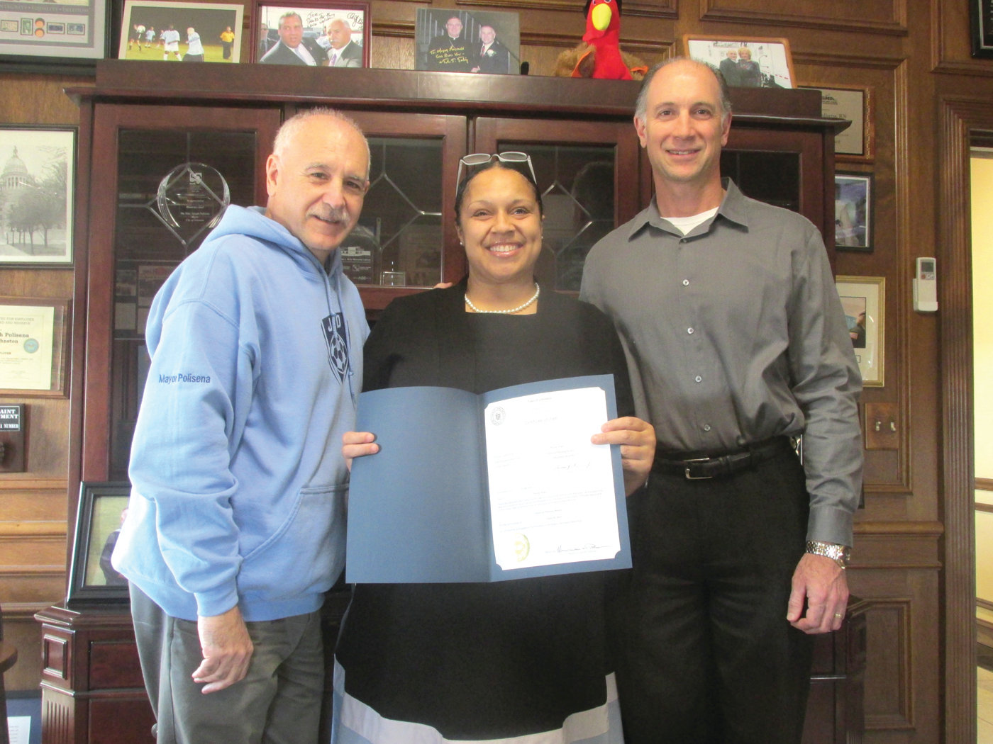 NICOLE'S NICHE:Flanked by Mayor Joseph Polisena and Town Clerk Vincent Baccari Nicole Pope is all smiles while holding the official citation declaring her as an official member o the Johnston Planning Board.