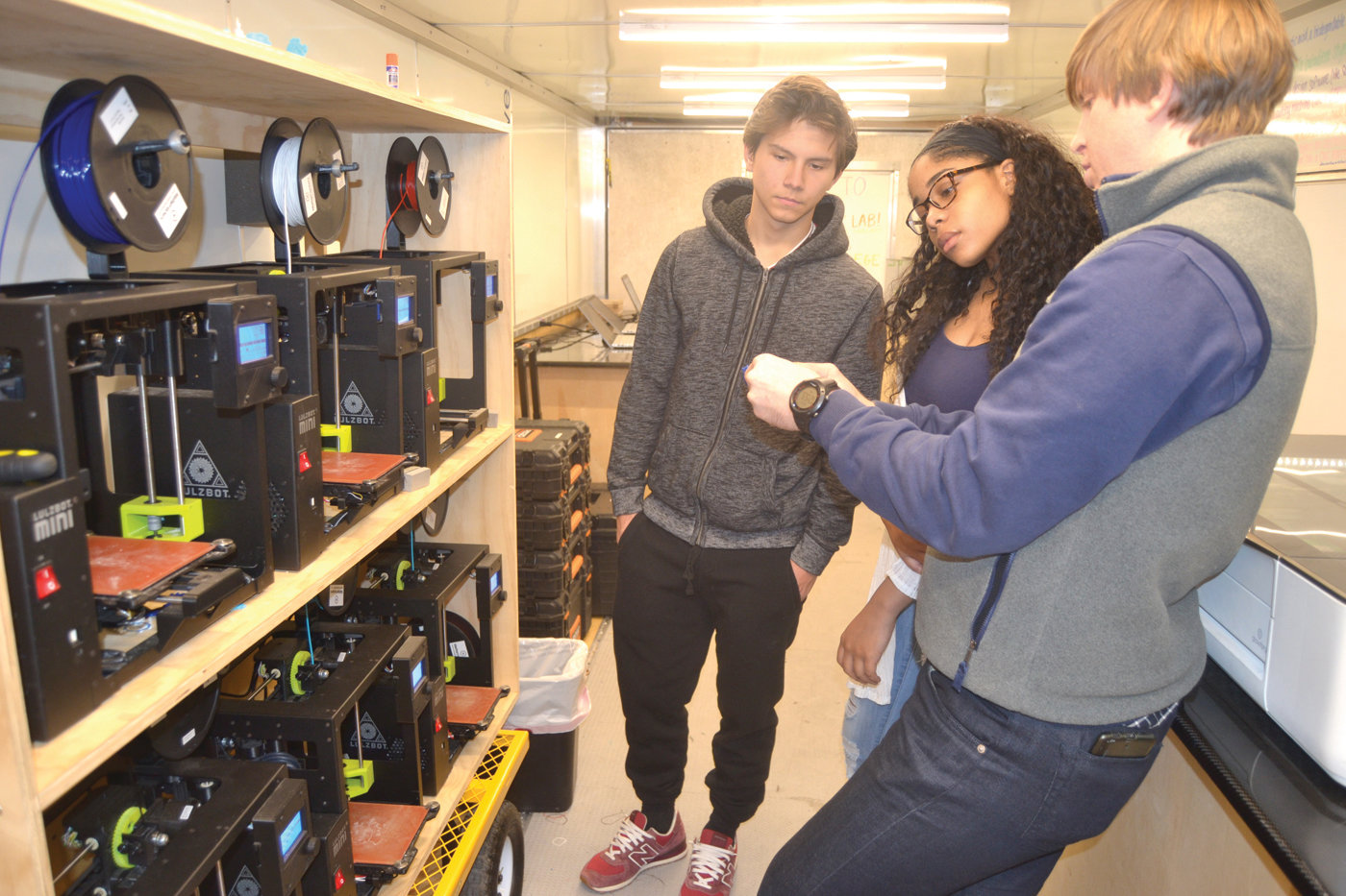 TALKING TECH: Seth Wiseman shows Myshelle Barron and Connor Agnew how a 3D printer is used to produce figurines and more.