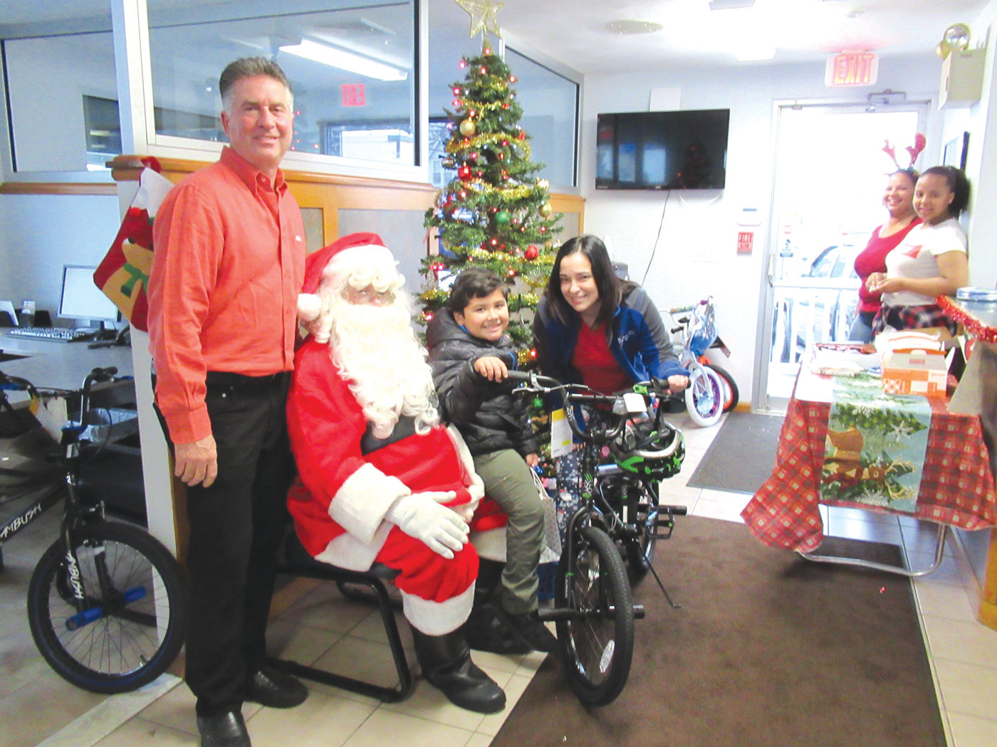 ROSALES' RIDE: Sergio Rosales, 6, a student at Sarah Dyer Barnes Elementary School in Johnston, sits stop his new bicycle inside Shannon Motors on Killingly Street and is joined by co-owner John Gosselin, Santa Claus and Office Manager Gina Amore