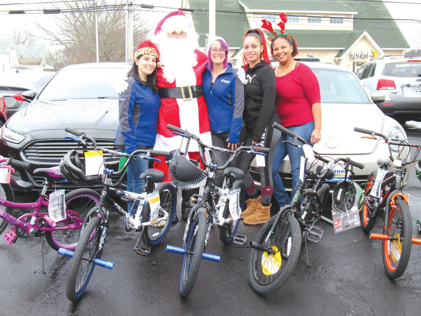 SANTA'S SUPER STAFF: Santa Claus made a special appearance for 25 children who won the used car company bike giveaway and is joined by helpers Anne Quinn, Dawn Lapan, Marenis Peralta and Williana Pimentel. (Photos by Pete Fontaine)