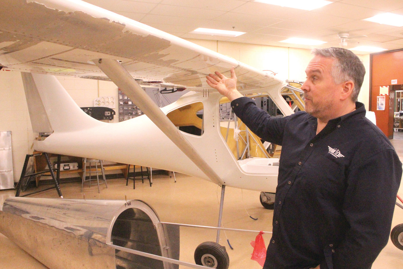 TAKING OFF: Aviation academy instructor Brian Lussier with the airplane that is now part of the classroom at the Warwick Area Career and Technical Center.