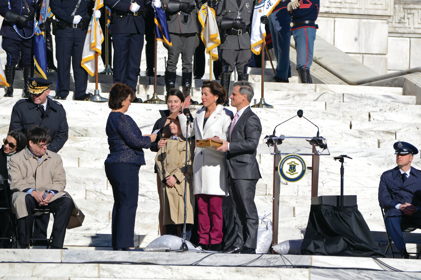 FOUR MORE YEARS: Governor Gina Raimondo, surrounded by family, is sworn in for her second term as Governor of Rhode Island by Secretary of State Nellie Gorbea, who was later sworn in for her new term by Raimondo.