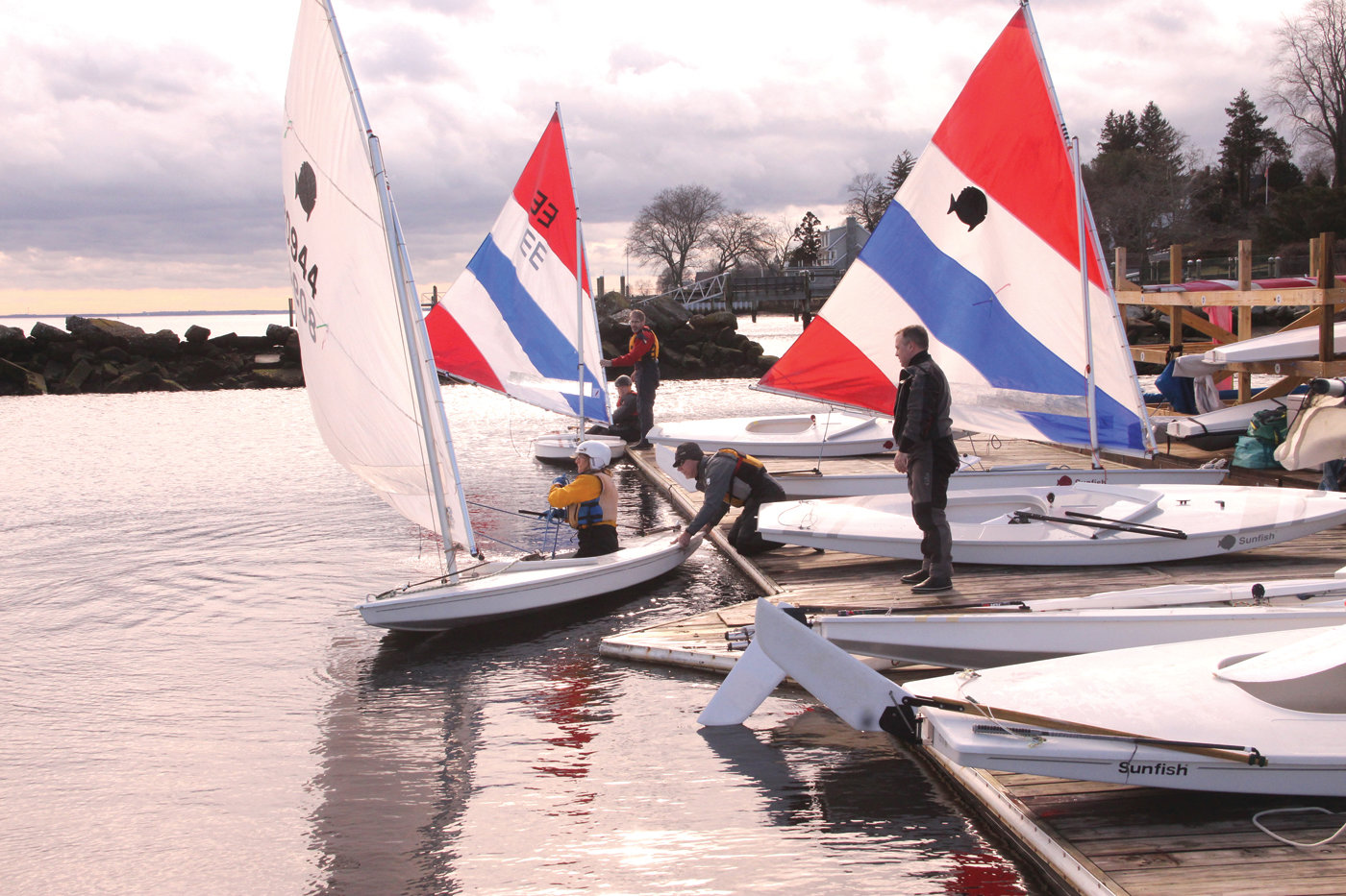 OFF TO THE RACES:  With assistance from fellow sailors, the fleet leaves the tranquility of the docks for open water.