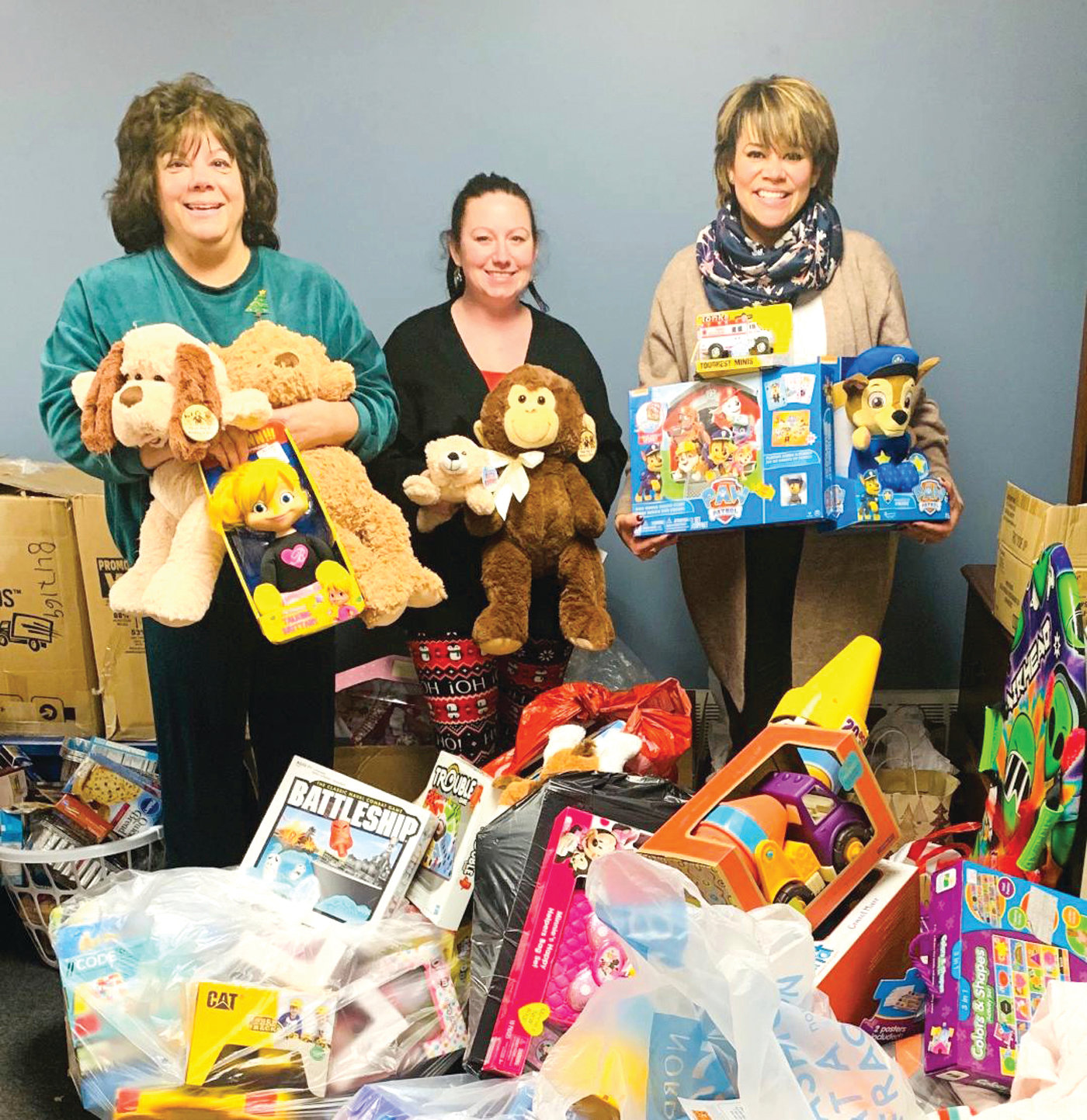 MAKING MORE SMILES: L-R, Joanne McGunagle, Executive Director and CEO of CCAP along with Taryn Gilchrist, from POCO LOCO and Lammis Vargas showcase some of the toys collected.