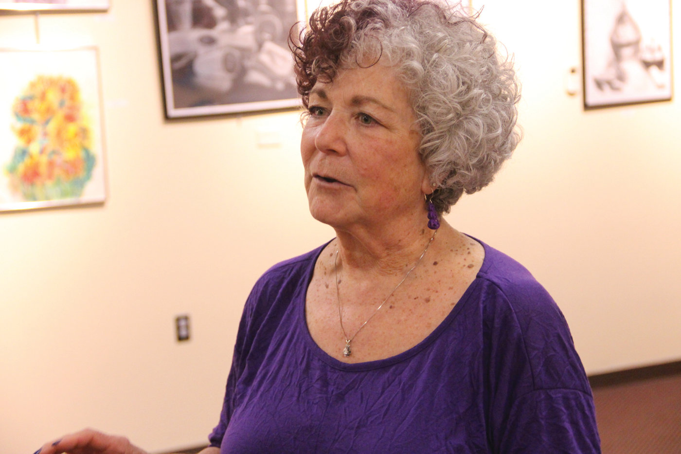 SPLASH OF COLOR: Barbara Rosenbaum and one of scores of her work now on display at the Cranston Public Library.