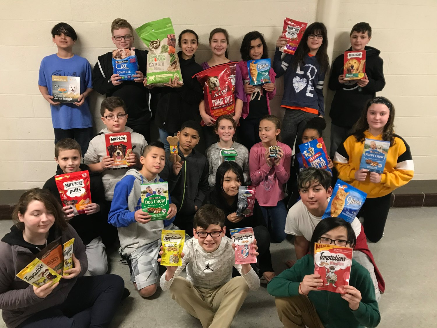 Students hold up donated items that would go to the East Greenwich Animal Protection League.