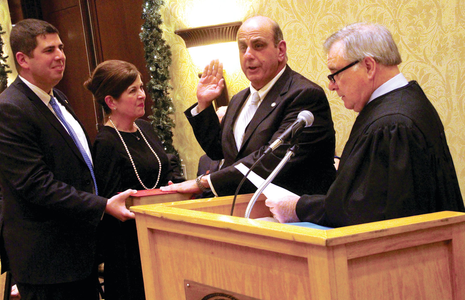 TAKING THE OATH: Associate Supreme Court Justice and former mayor Francis X. Flaherty administers the oath of office to Mayor Solomon as his son, Rep. Joseph Solomon Jr., and wife Cynthia look on.