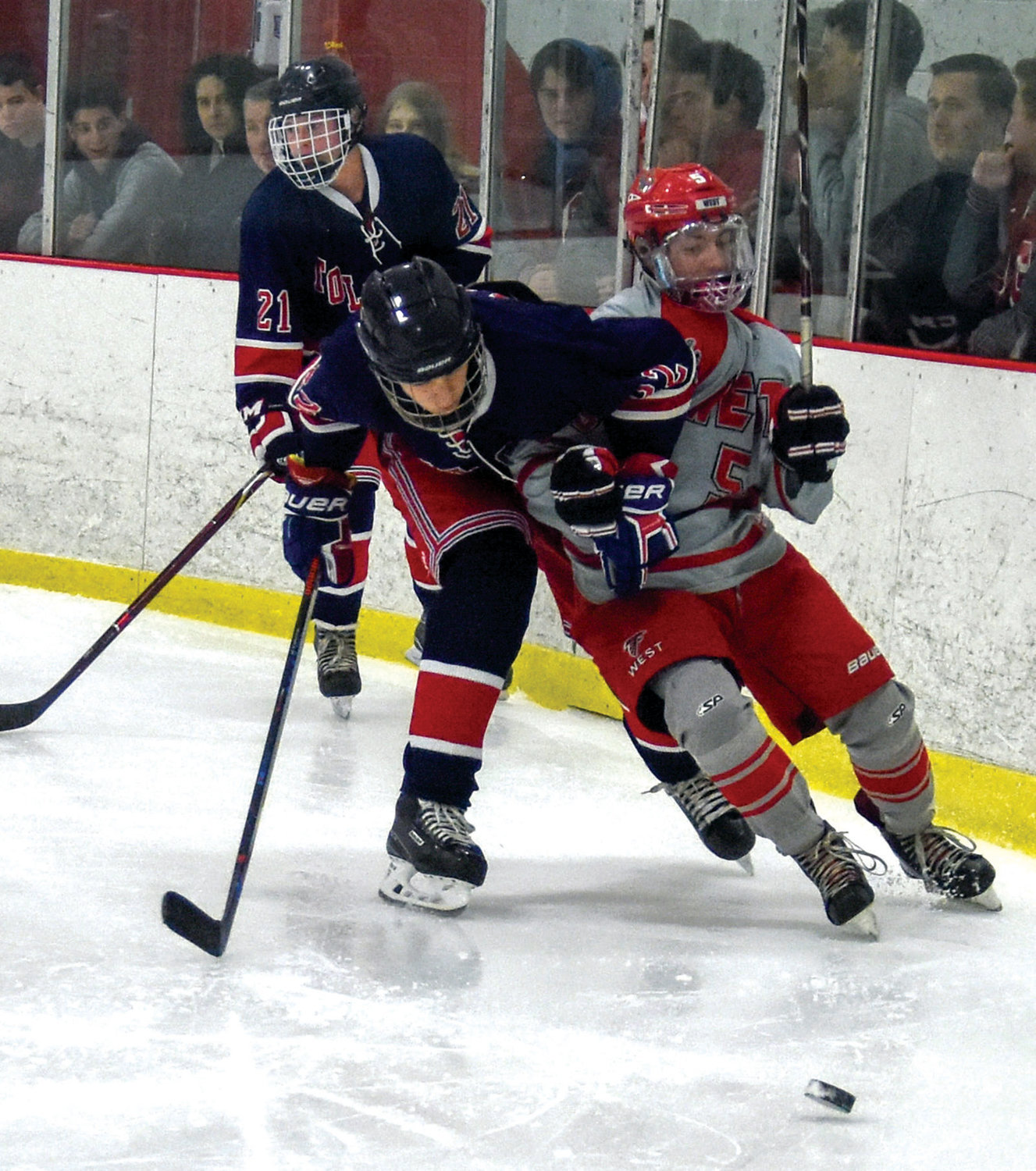 ALONG THE BOARDS: Cranston West's Max Savaria battles against a Toll Gate defender during their matchup last week at home. West took home a 7-4 win.