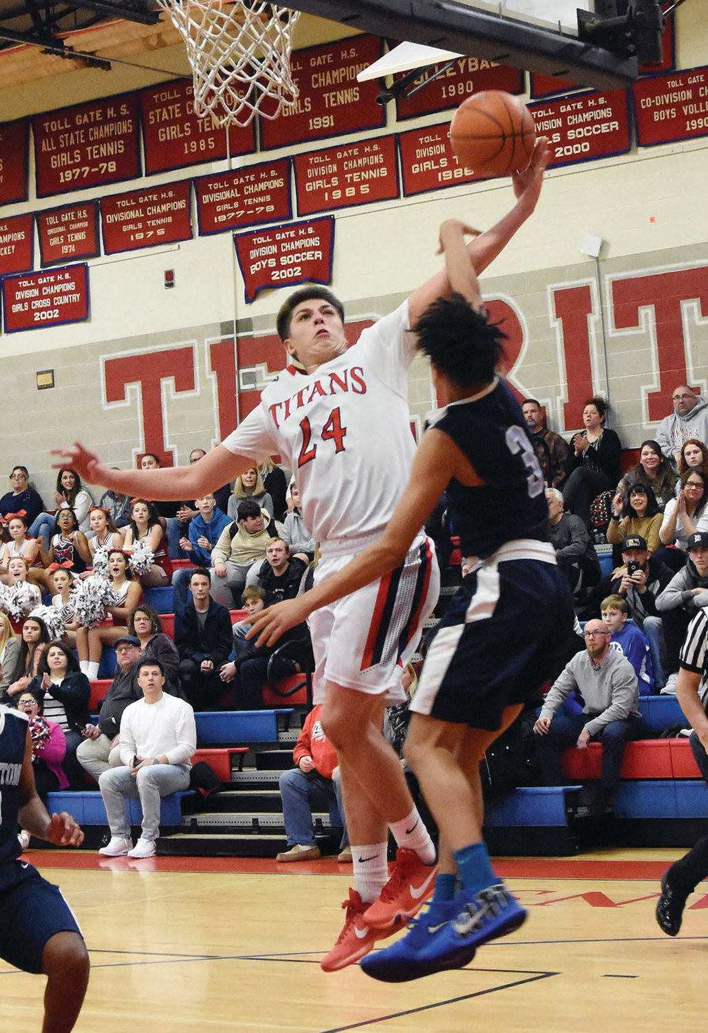 REACHING A MILESTONE: Toll Gate's Brandon Scott puts up a shot over a Johnston defender on Tuesday evening at Toll Gate. Scott, a senior, sank a 3-pointer to hit and surpass 1,000 career points for the Titans.