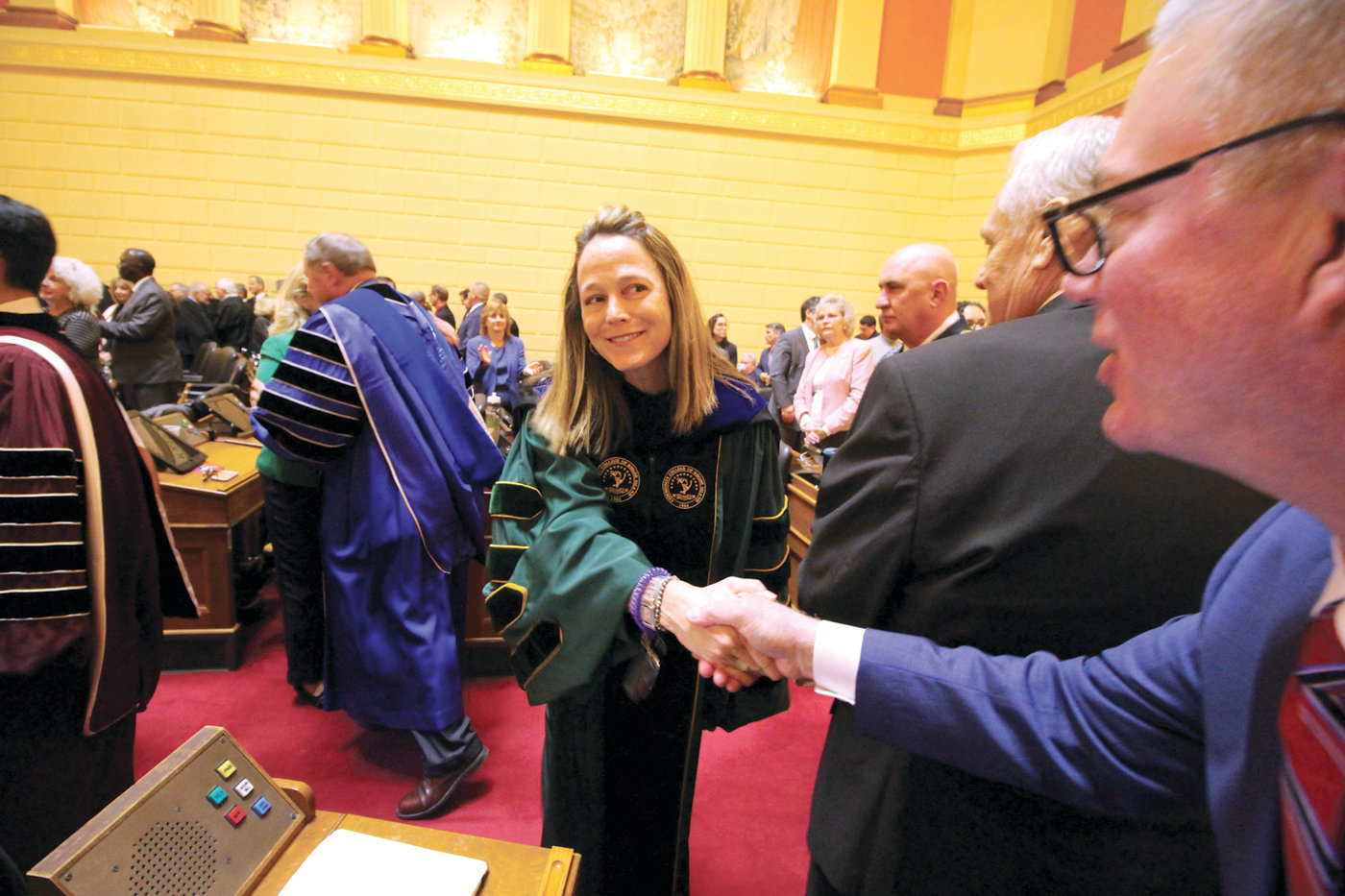WELCOME: Warwick Rep. Joseph McNamara and fellow legislators greeted state department directors as they entered the chambers Tuesday for the governor's State of the State address. Here, McNamara shakes hands with CCRI President Meghan Hughes.