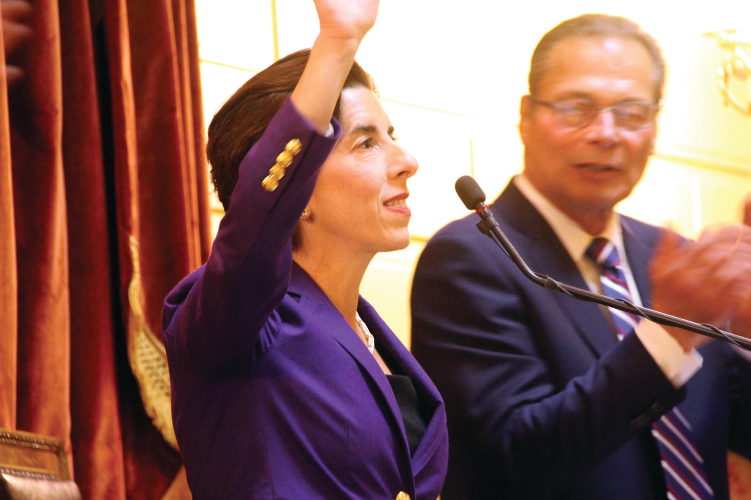 RECOGNIZING THE APPLAUSE: With Senate President Dominick Ruggerio at her side, Gov. Gina Raimondo waves to assembled legislators, state officials and a full gallery of spectators before speaking Tuesday.