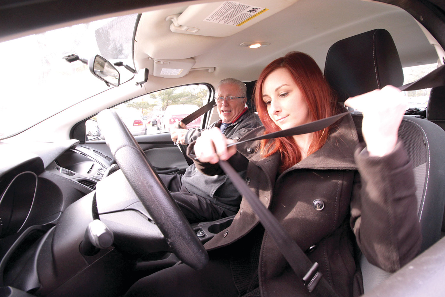 "FIRST AND FOREMOST: Stephen Fenton, a AAA Northeast driving instructor for the past 15 years, buckles up with Kayla Broadmeadow, also of AAA, before going though his routine for student drivers. He said many students come to him ""road read"" having had practice driving lessons from family members, which he recommends for beginners. One of the first rules he tells students is to tell others on the road, ""where you are going - signal."" He said students have the most difficulty with merging."
