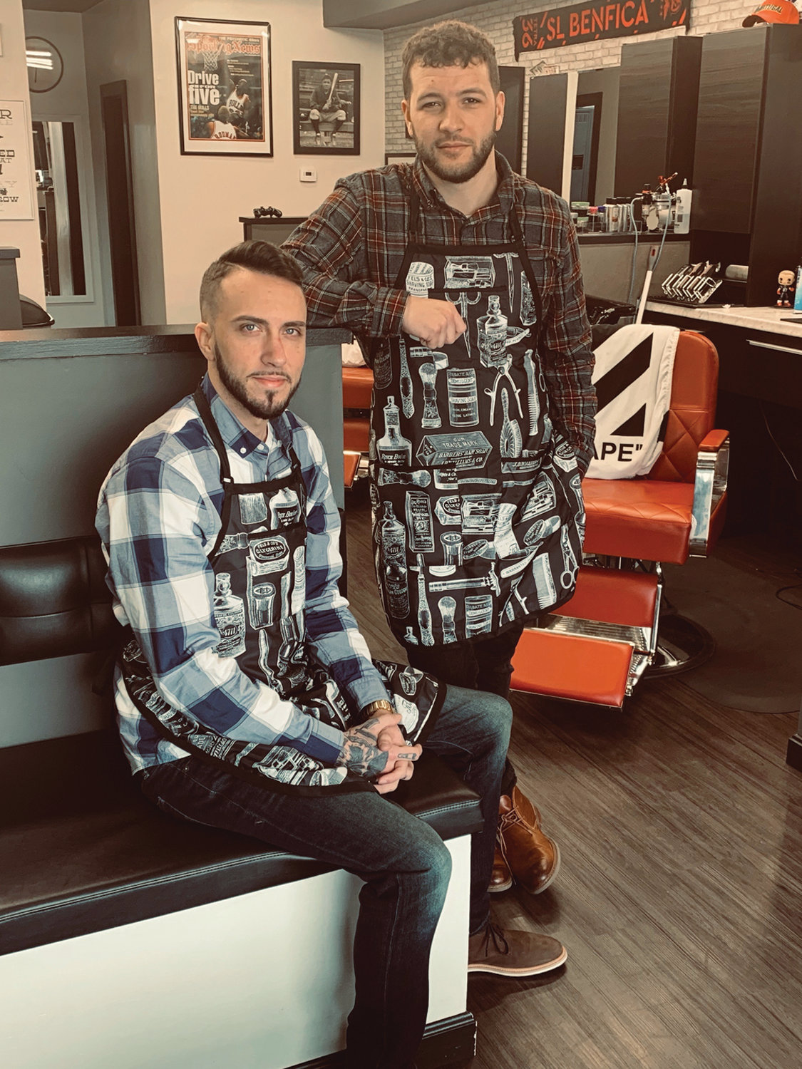 "Bobby Lima (seated) and fellow barber Jared Rodrigues, who have realized a lifetime dream with the opening of ""The Spot,"" welcome you to their modern yet classic barber shop on Warwick Avenue."