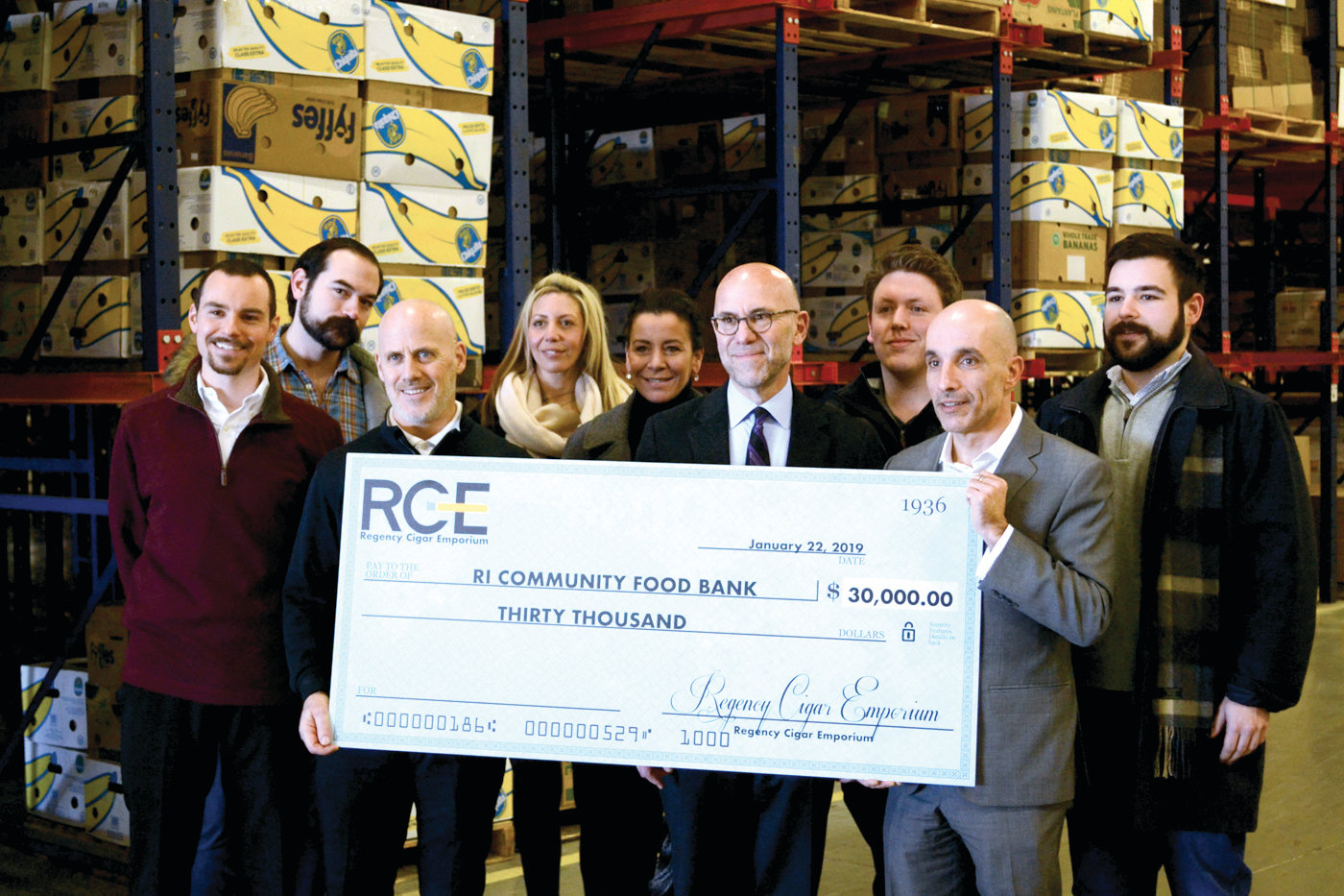 QUITE A BOOST: Tyler Divona, Stephen Carlson, Andrew Schiff (RI Food Bank CEO) Michael Correia (Owner, Regency Cigar), Antonio Negovetti, Talia Morettia, Melissa Stephens, David St.Amant and Brandon Ribbing celebrated a big donation with a big check.