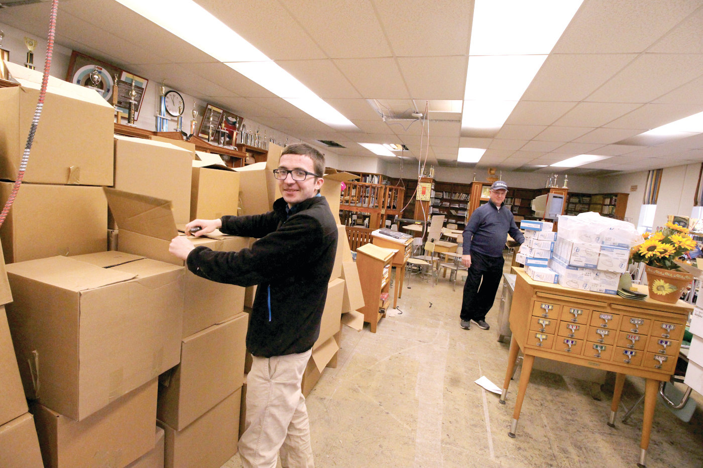 THINKING CHRISTMAS: Cody DiLibero and Joseph Luszcz break down cardboard boxes that had been used for storage of books for a second use during the church Christmas bazaar.