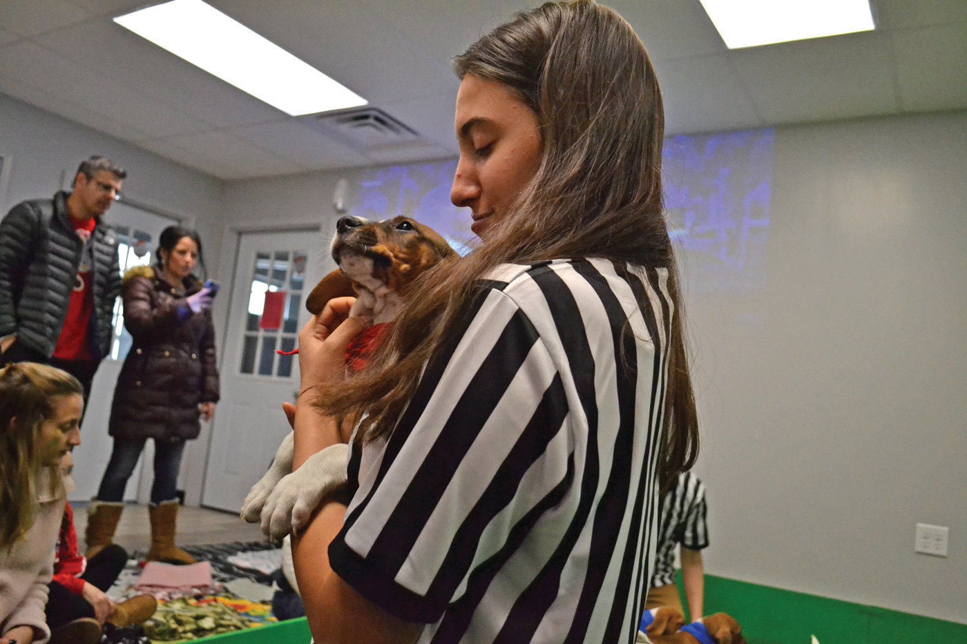 KEEPING THEM CONTAINED: Victoria Minicucci, a shelter volunteer, had the enviable role of a referee, which basically meant she got to cuddle the puppies that tried to escape from the turf field enclosure in the heat of their playing.