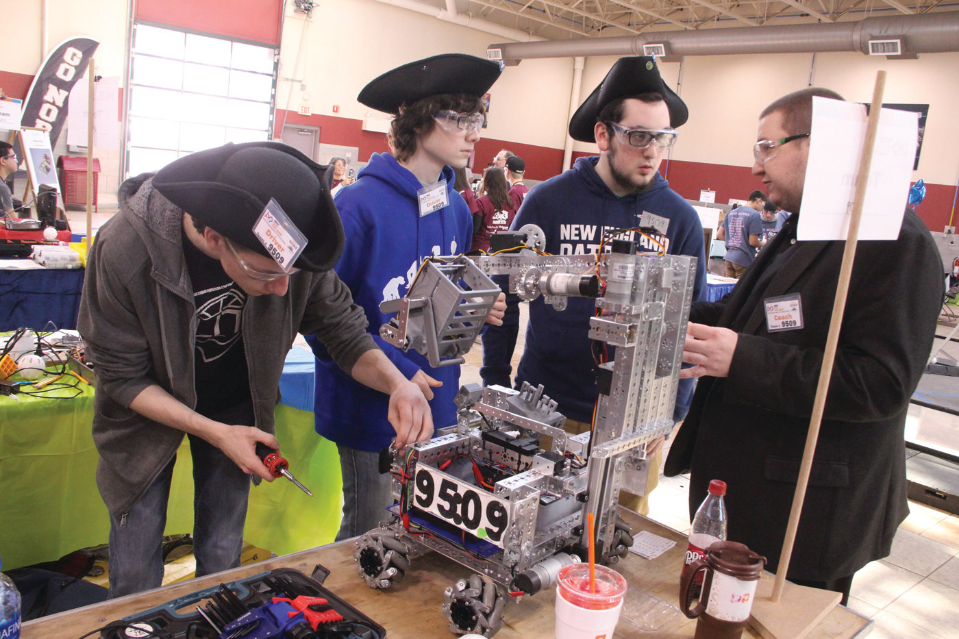 THE PATRIOTS: Pilgrim High School team Patriots make adjustments to their robot with the advice of coach Chris Uth. Pictured from left are Jacob Trivisonno, Kyle Pincins and Ben Smith.