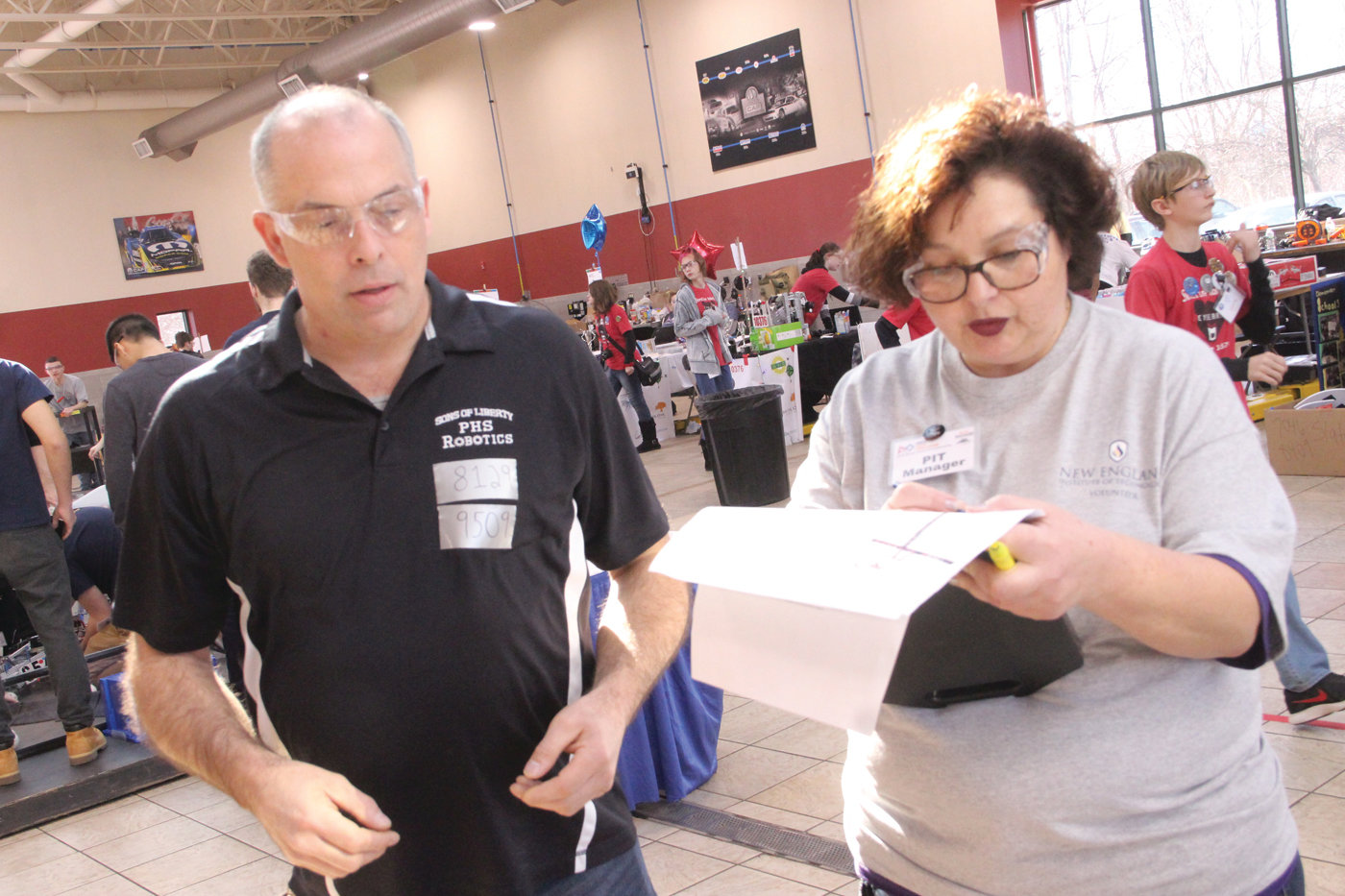 "GETTING IT STRAIGHT: Pilgrim robotics teacher Larry West gets the schedule of events from pit manager and self-proclaimed ""Robotics Mom"" Ines Loureiro, a volunteer from the Mt. Hope team."