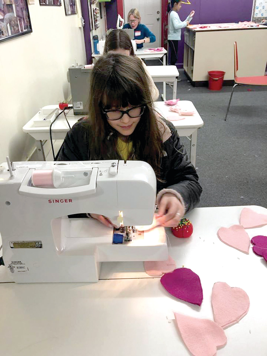 165 HEARTS LATER: Dozens of participants gathered together to create nearly 200 hand warmers at the sewing school in just under three hours.