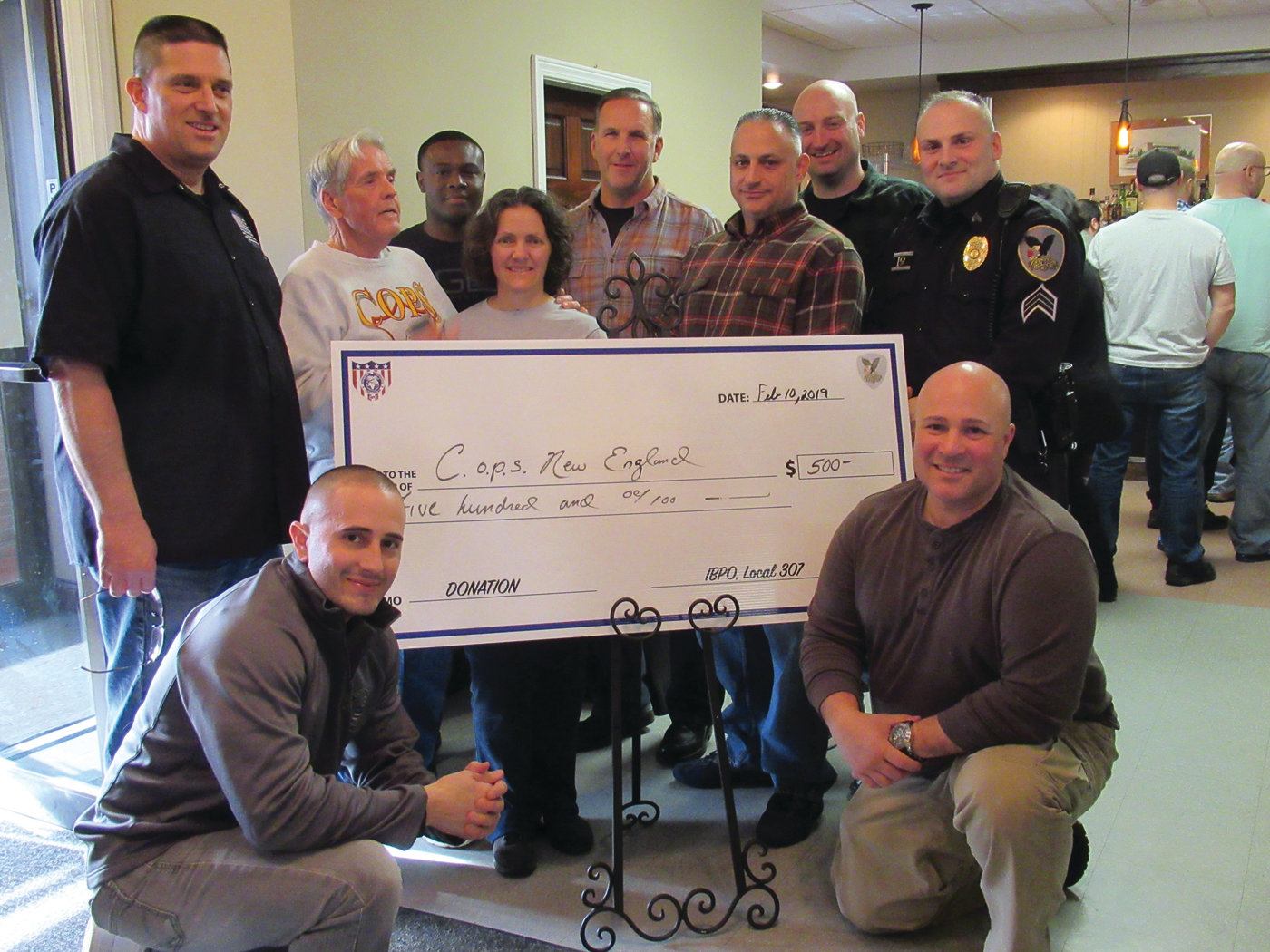 CHECK PRESENTATION: Robert Shaw, father of the late Providence Police Sgt. Steven M. Shaw, and his wife, Maria, are joined by IBPO Local 307 members during Sunday's check presentation to COPS. Pictured, kneeling in front, are patrolmen Arthur Petteruti and Mario Mennella, and standing, Sgt. Joe Scichilone, Patrolman Derek Ofori, Detective Brian Loffredi, Patrolman Mike Andreozzi, Capt. Matt Benson and Sgt. David Loffler.