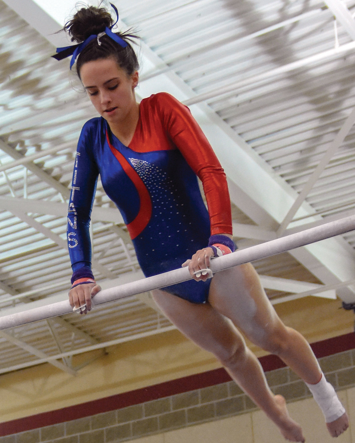 HANGING OUT: Warwick's Olivia Paquet does a routine on the bars at the state championships.