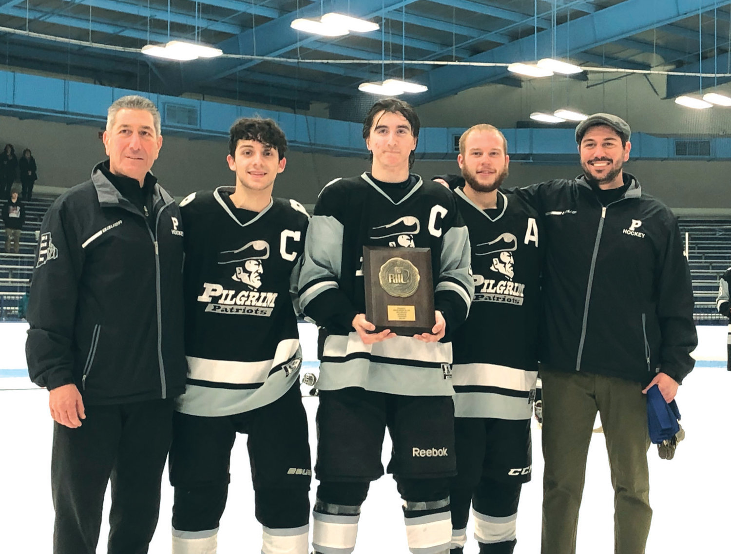 LEADERS OF THE PACK: Pilgrim senior captains Matt Pacheco, Jack Clements and Ryan Pietros accept the Rhode Island Interscholastic League Division III Championship plaque presented to them after topping West Warwick/ Exeter-West Greenwich on Saturday at the Boss Arena at URI. Also pictured are coaches Mike Boyajian Jr. (far right) and Mike Boyajian Sr. (far left)