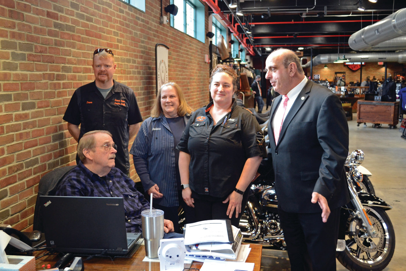 FAMILY BUSINESS: First generation owners Russ and Barbara Hamptom pose with their second generation, daughter Amy Bishop (owner) and her husband Dana, along with Mayor Solomon during his visit to Russ' Ocean State Harley-Davidson on Tuesday.