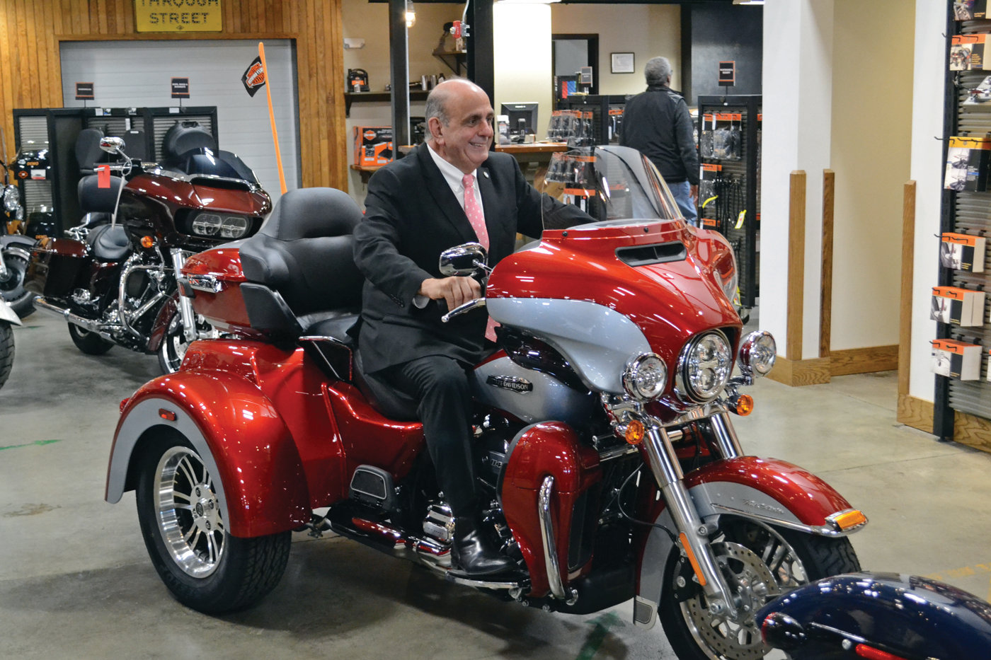 KID IN A CANDY STORE: Mayor Joseph Solomon was beaming like a child on his first bicycle behind the handlebars of this cherry red Tri-Glide, in the main showroom of Russ' Ocean State Harley-Davidson.