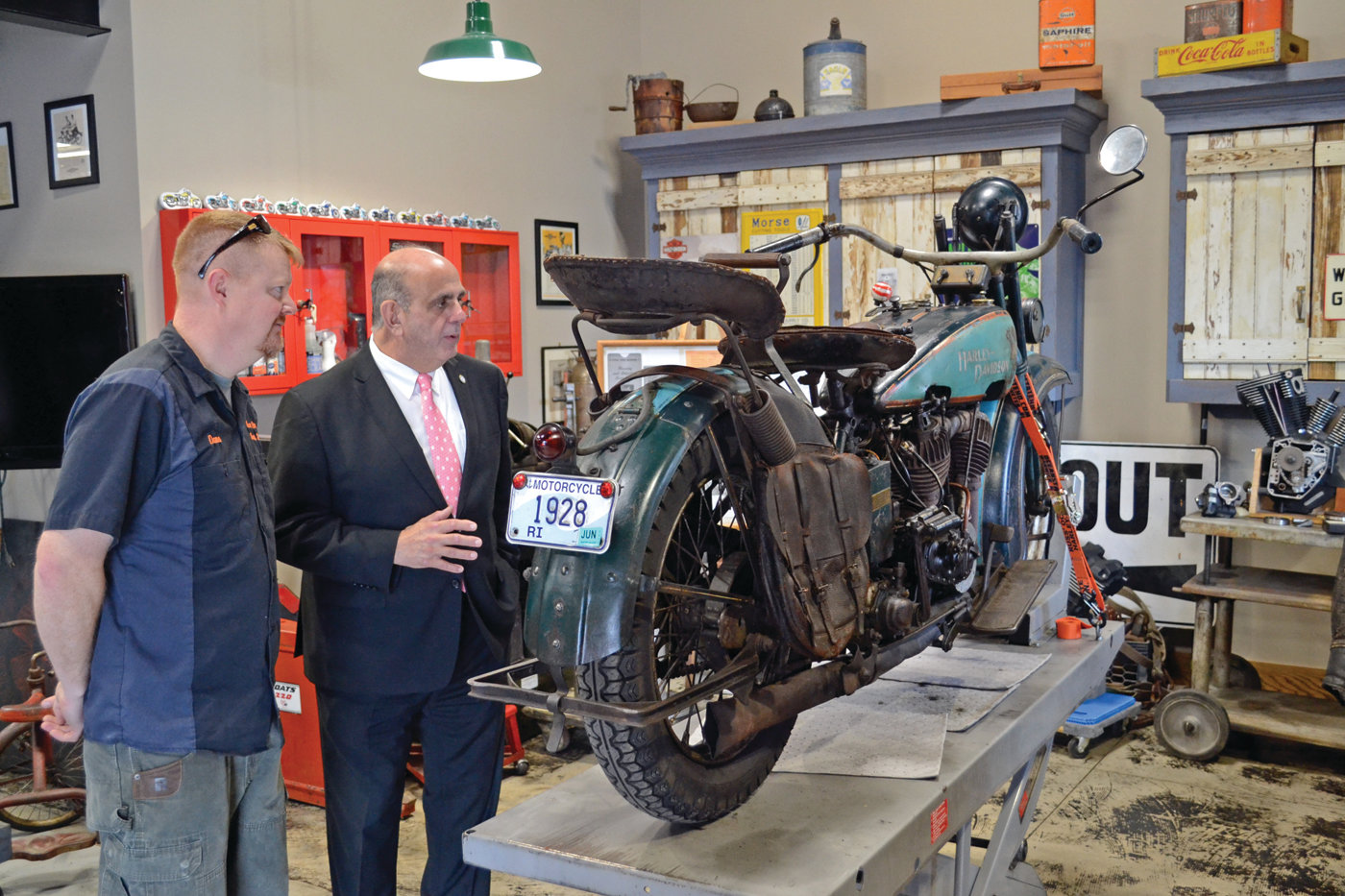 DON'T MAKE EM' LIKE THIS ANYMORE: Mayor Solomon talks with Dana Bishop, husband to owner Amy Bishop and the director of marketing, about the custom 1928 Harley-Davidson on display in their showroom.