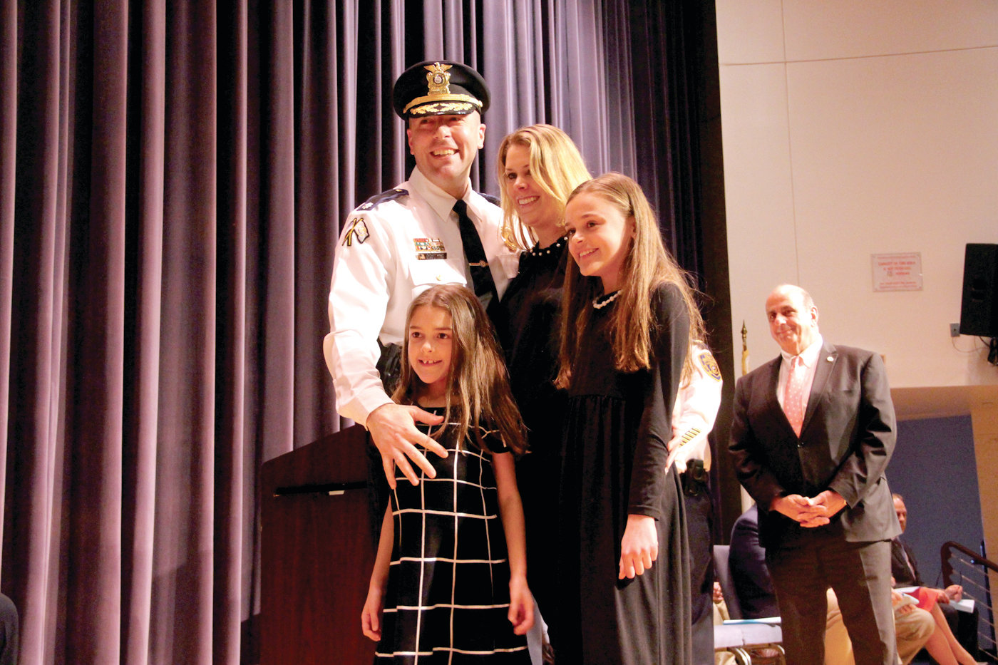 LOTS OF SUPPORT: Deputy Chief Mark Ullucci is joined by his wife, Sylvia, and daughters, Audrina and Sabrina, on stage at the ceremony.
