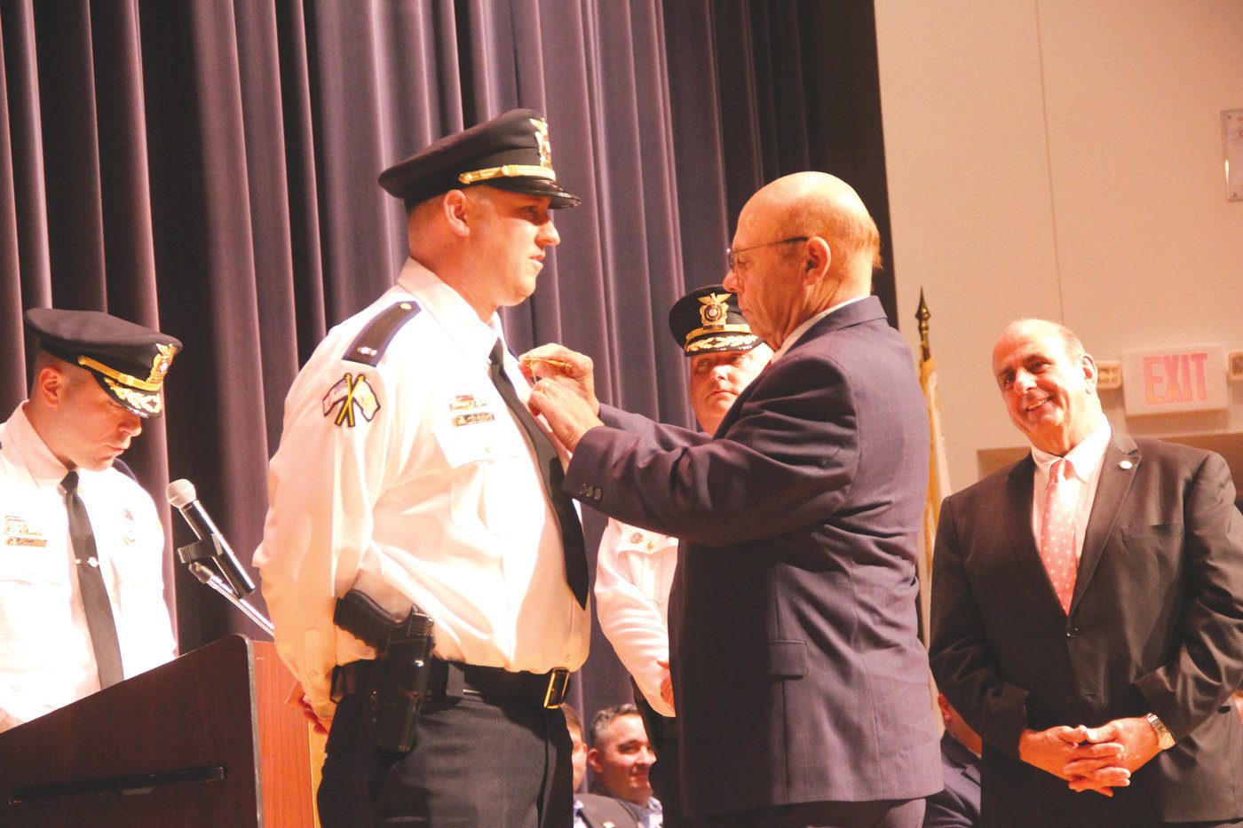 FATHER TO SON: Former Warwick Police Chief William DeFeo pins the lieutenant badge on his son, William Jr.