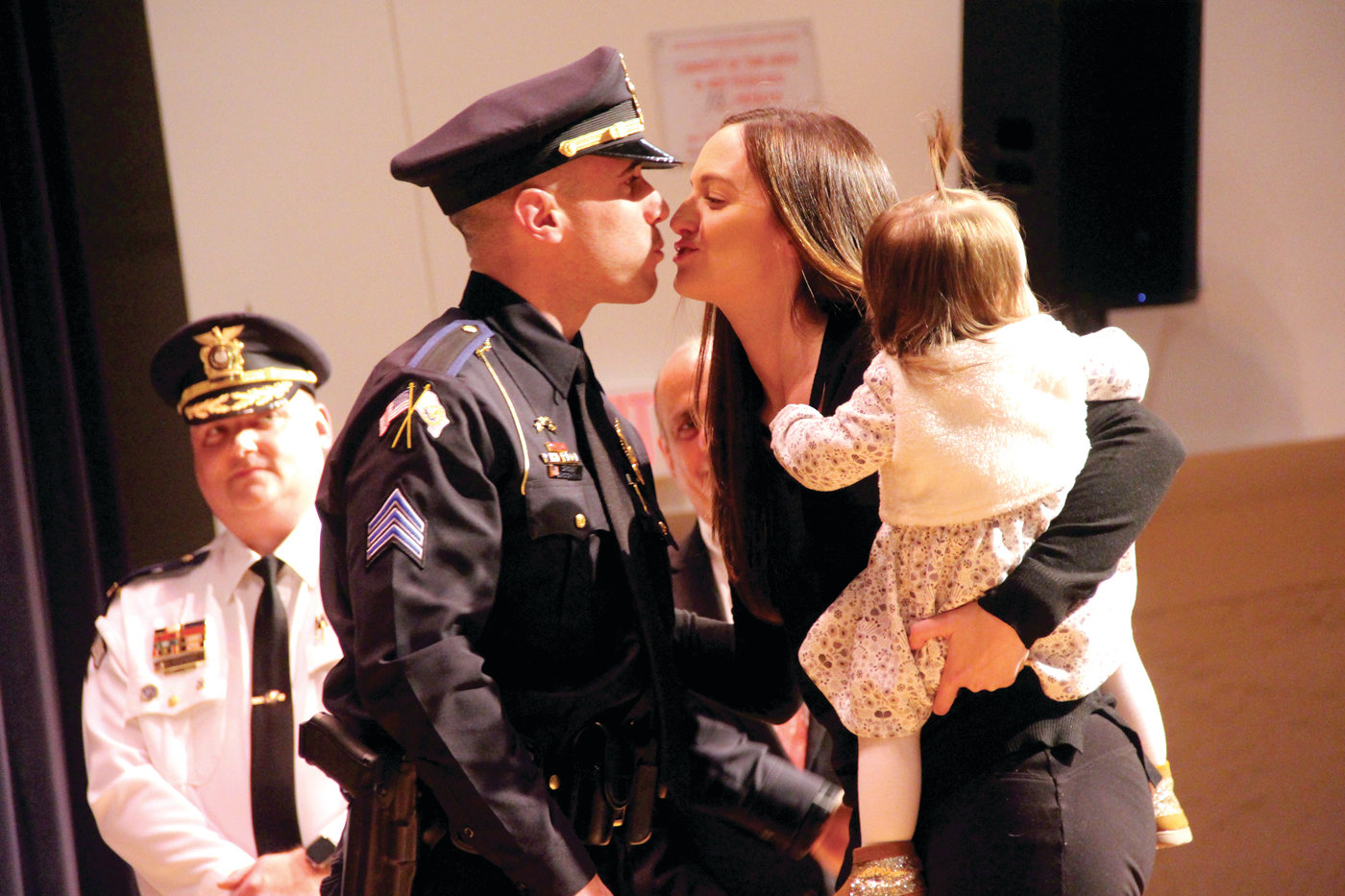 A KISS, TOO: Sgt. Christopher Lo gets a kiss from his wife, Diana, after she pinned on his badge. She is joined by their daughter, Brynley.