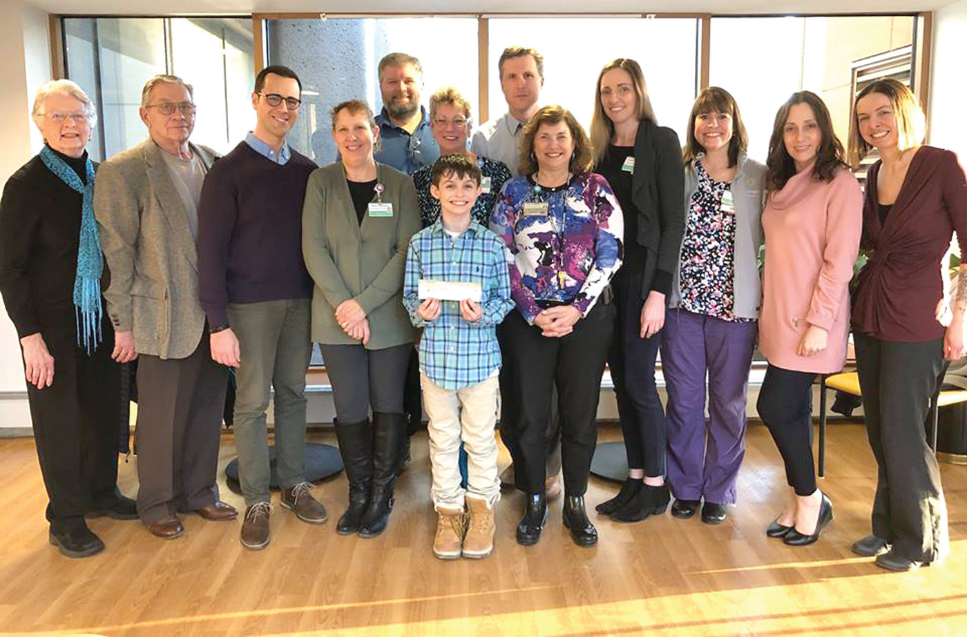COMING TOGETHER: NEHA Executive Director Rich Pezzillo (third from left) accepted a check for $5,200 from Salisbury Farm during a ceremony at the Rhode Island Hemostasis and Thrombosis Center on March 13. Dylan Holland, a boy with severe hemophilia from Burrillville (middle), cut the ribbon the corn maze back in October.