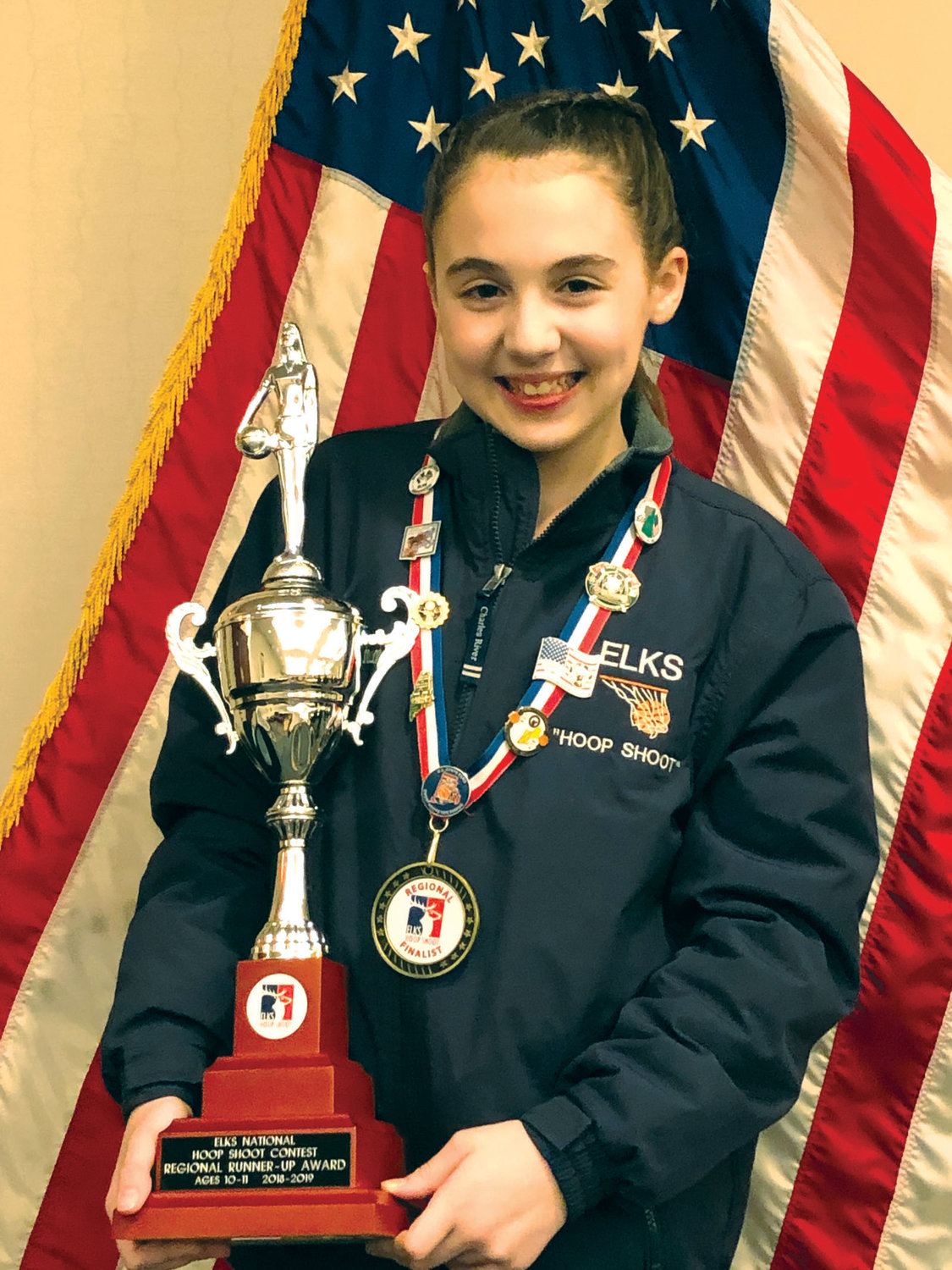 SUPER SHOOTER: Warwick's Sarah Berube, 11. is all smiles moments after receiving the prestigious New England Elks Hoop Shoot Champion runner-up trophy and medals during Saturday's awards ceremony inside Deering High School in Portland, Maine.