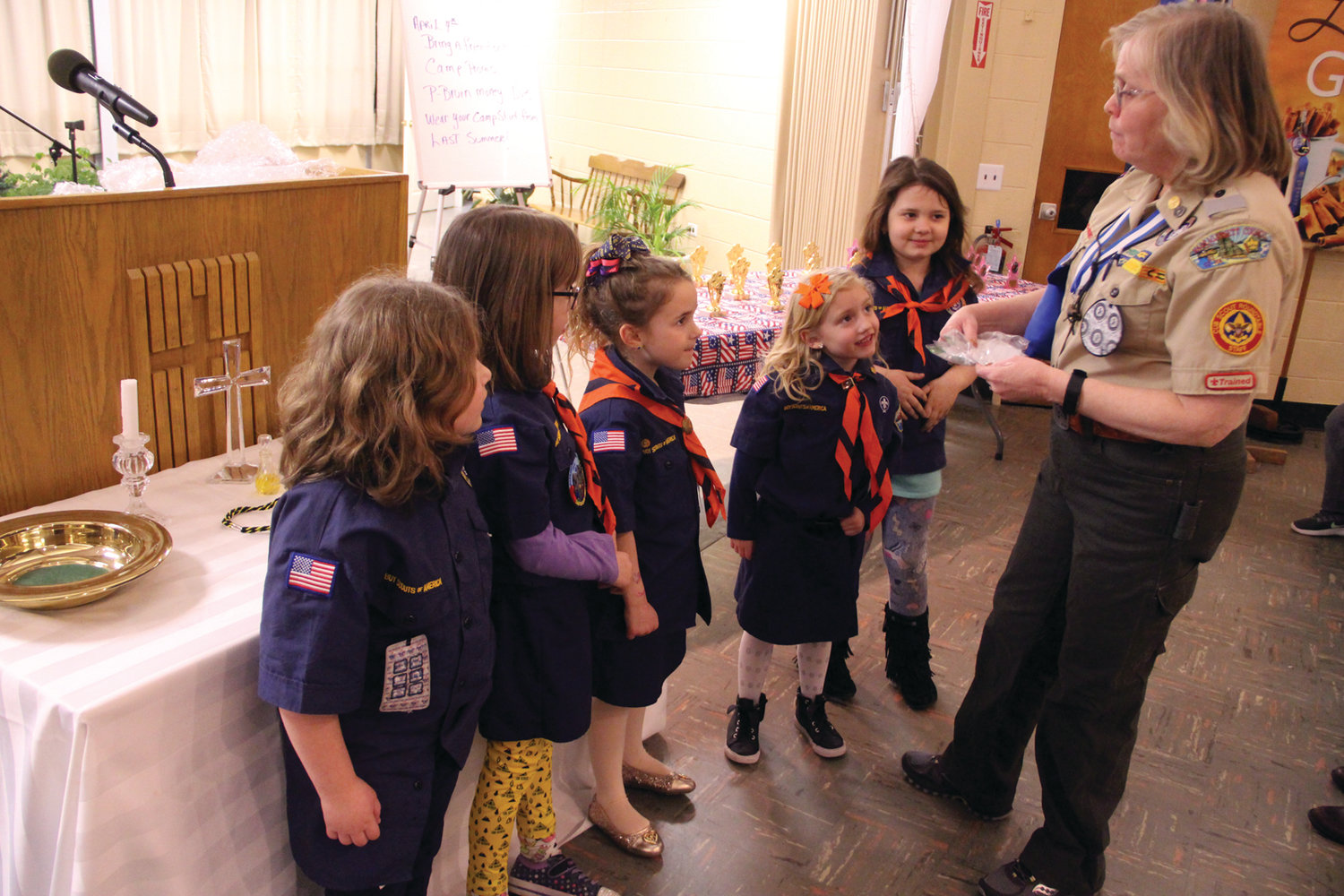 Den Leader Patty Gomm awards badges to members of her Cub Scouts pack.