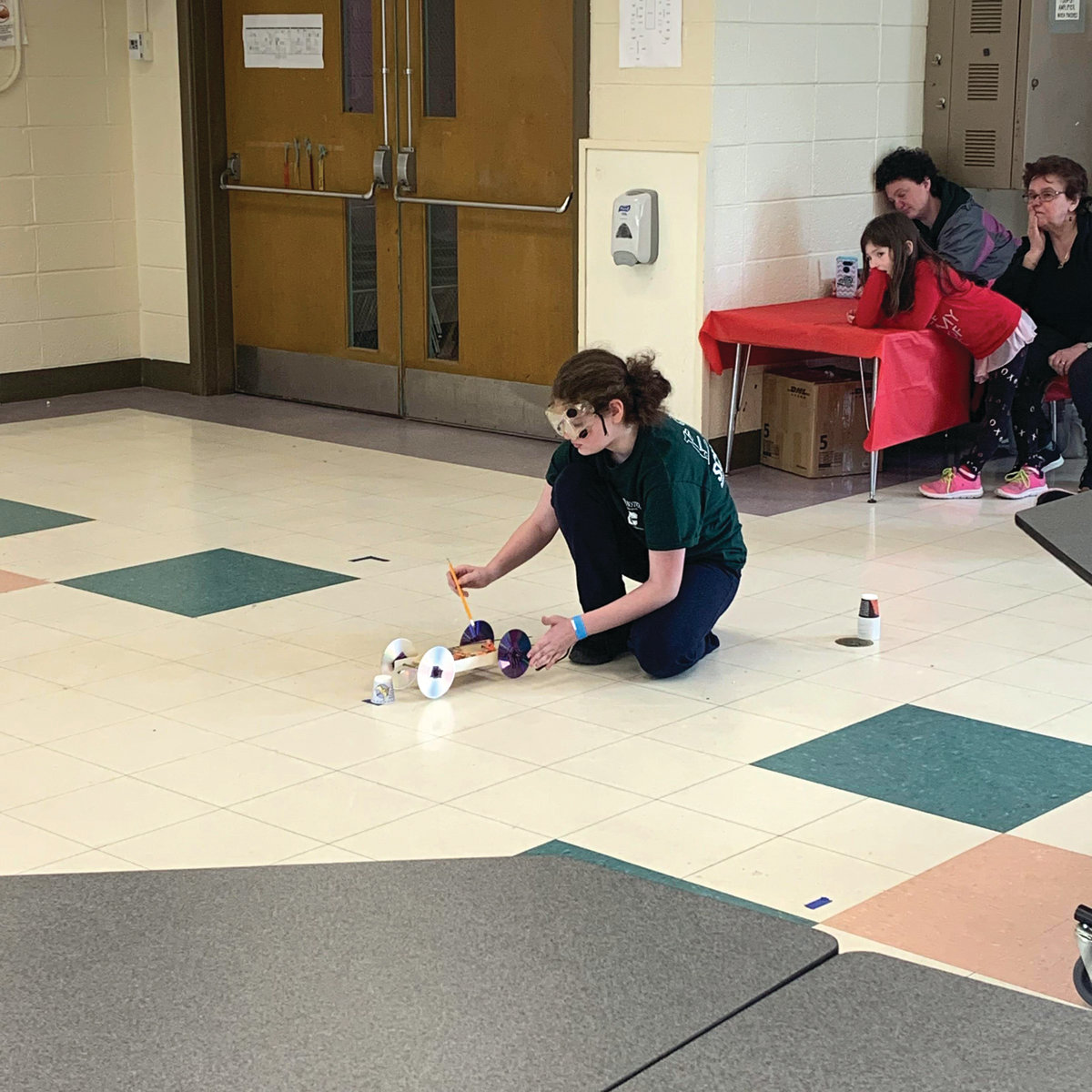 DETERMINATION: Cranston East junior Rose Lovenbury launches her mousetrap vehicle Saturday as her family looks on.