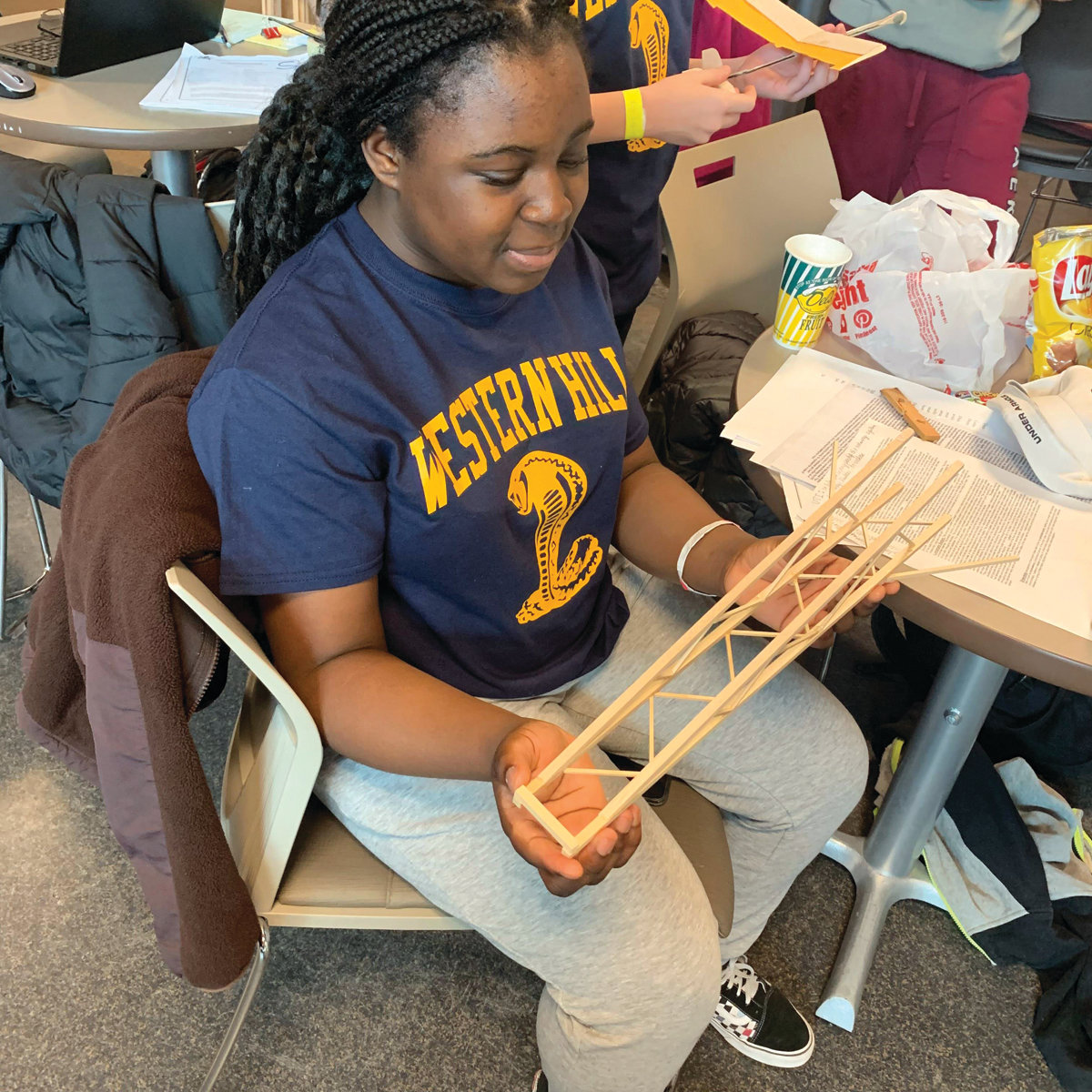 BUILDING SKILLS: Western Hills eighth-grade student Semiha Salami displays her team's Boomilever structure on Saturday.