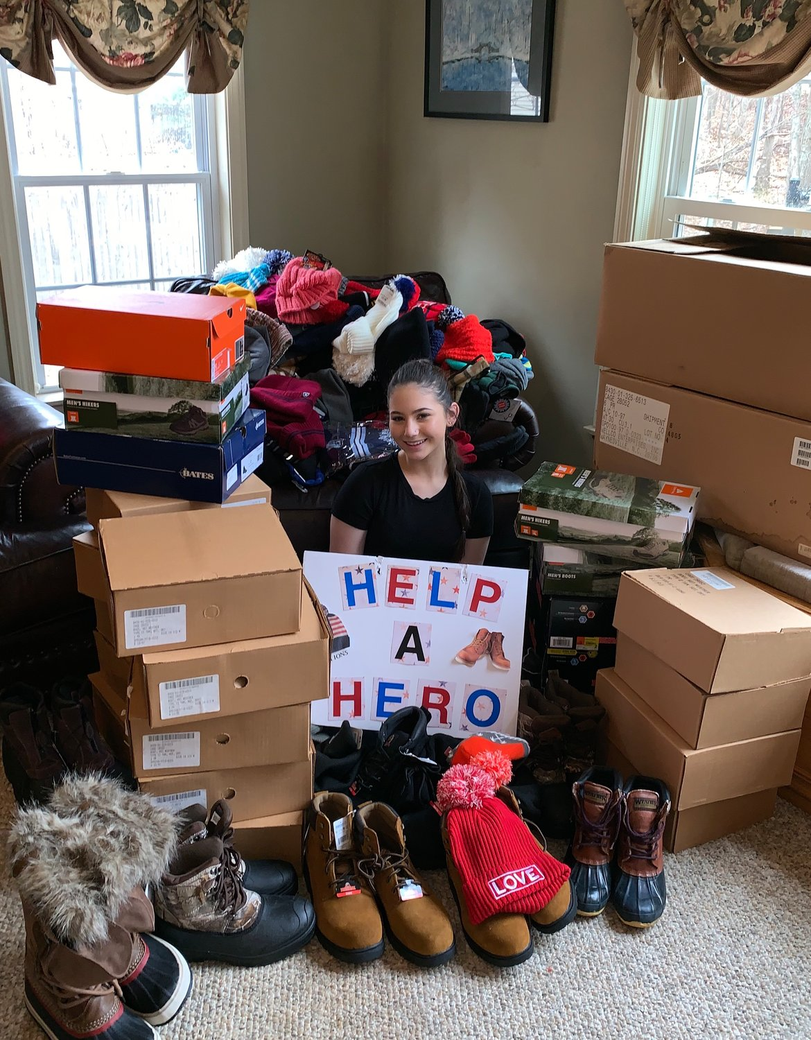 BOOTS ON THE GROUND: Ava Librizzi, a Warwick native and St. Raphael Academy junior, is eclipsed by a massive pile of donated boots and hats, amounting to over $8,000 of product in about three months of seeking donations.