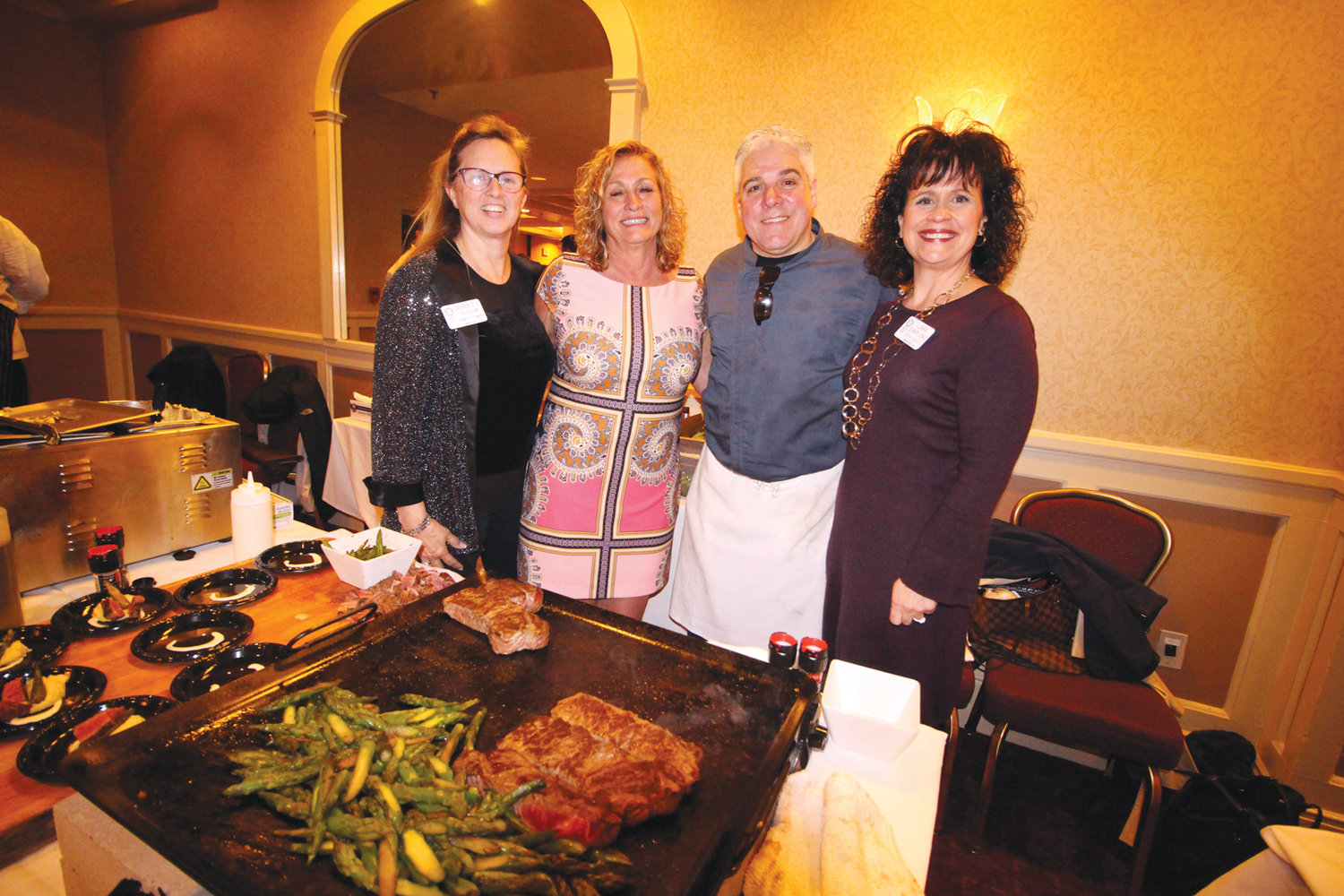 GALA TEAM: Dean Scanlon of the Revolution in Pawtuxet takes a break from carving filet minion that was served with asparagus to join for a group photograph with Janis Constantine, gala co-chair to his right and team members Lauren Slocum (left) and Lara D'Antuono.