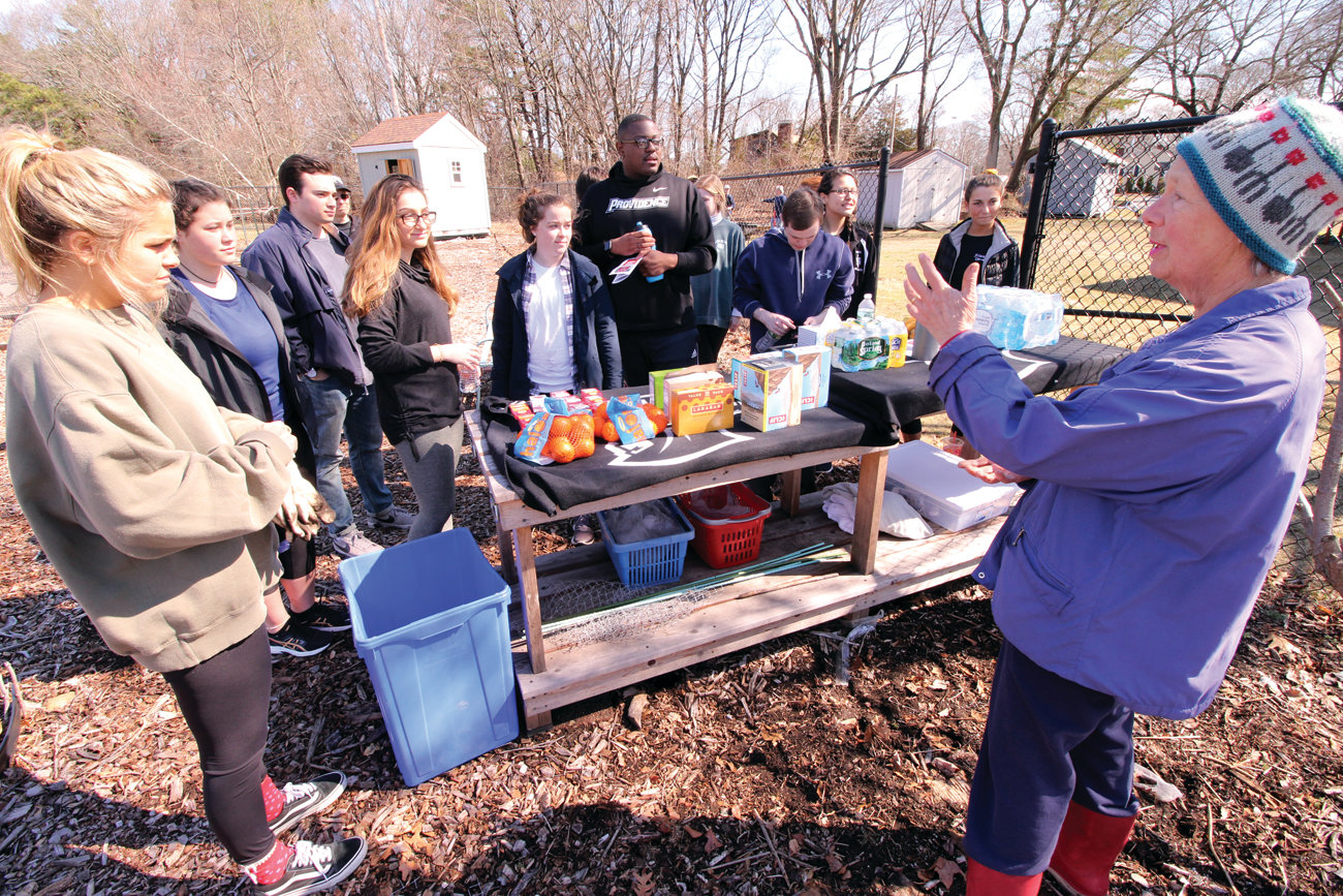 AN ARMY OF HELPERS: Barbara Melone addresses PC students before they tackled their assigned tasks at the Sts. Rose & Clement Parish Garden Saturday morning.