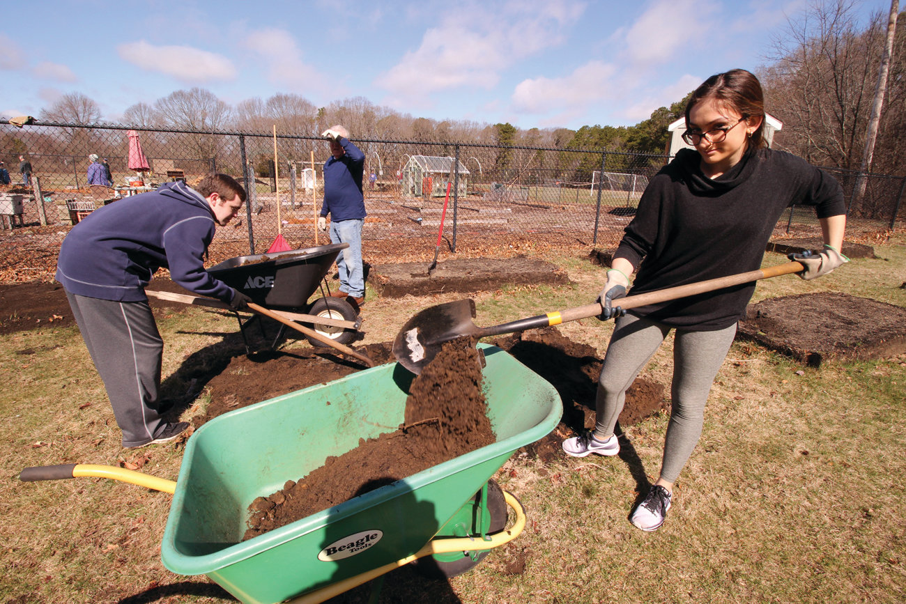 DIRT ON THE MOVE: PC students Connor Zimmerman and Alexandra Lima helped relocate raised garden beds at the Sts. Rose & Clement Parish Garden.