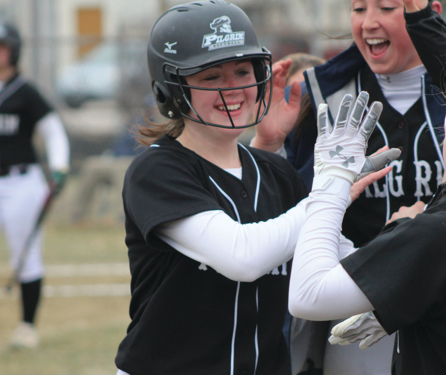 RALLY TIME: Pilgrim's Lily Brown celebrates with teammates after reaching home.