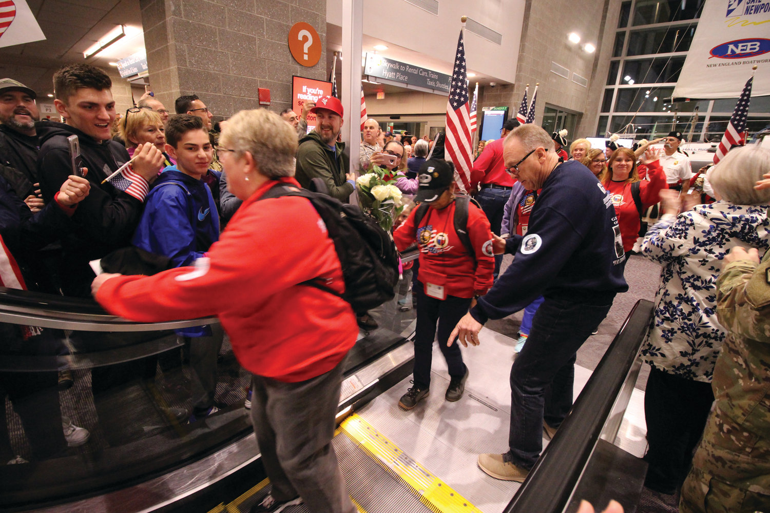WATCHING EVERY STEP: George Farrell, leader of the Rhode Island Honor Flight, doesn't let up for a moment during the day-long event. Here he helps guide veterans as they arrive to a tumultuous reception at Green Airport.