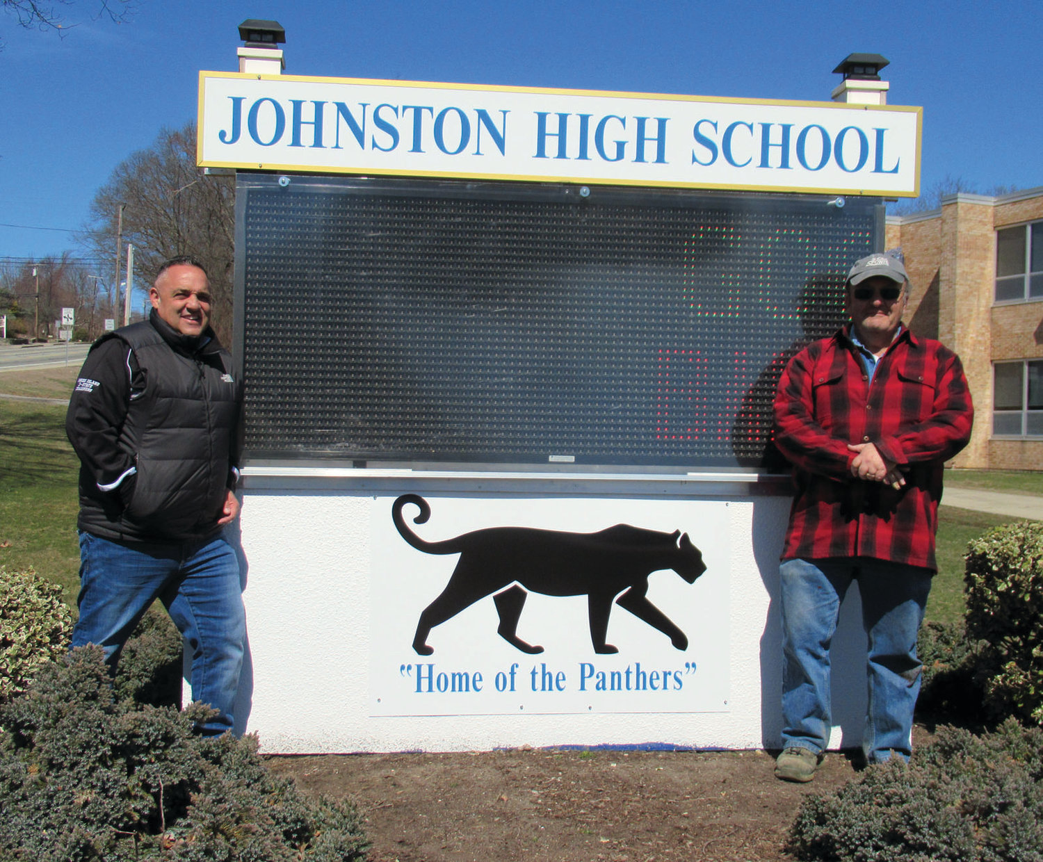 GRAND GIFT: Gary Salzillo, left, stands next to the digital sign he donated to Johnston High School. John Eramian, right, designed, constructed and donated the frame that surrounds the sign.