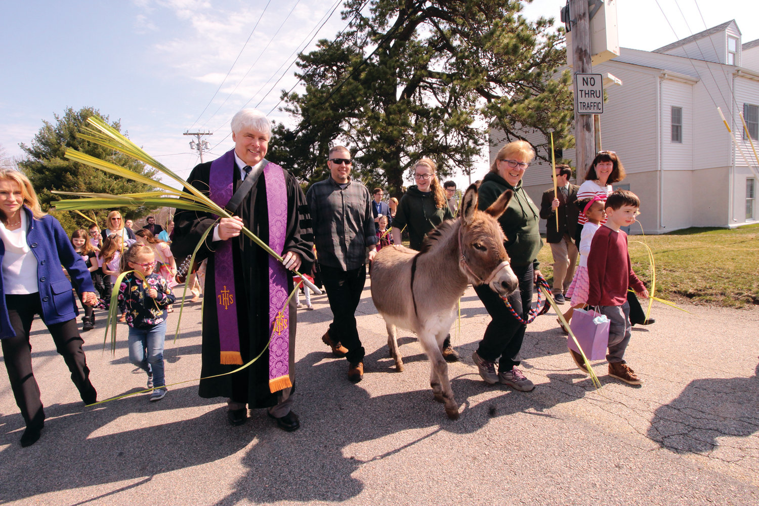 TAKING THE LEAD: With Hannah the Jerusalem donkey and Pastor Stephen Clark in the lead, Greenwood Community Church, Presbyterian parishioners circled the church as part of Palm Sunday services.