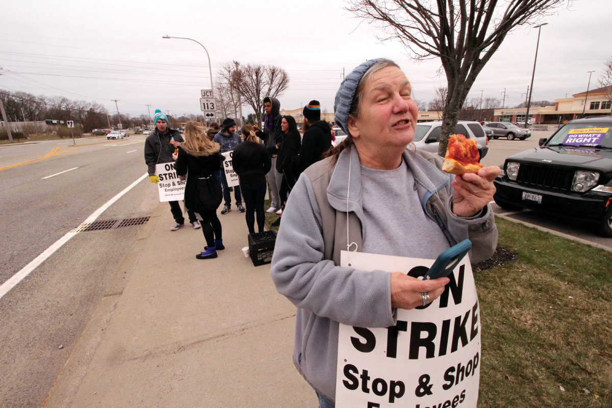 READY TO GO BACK TO WORK: Linda Fry, who has worked at Stop & Shop for 30 years, gets a bite of pizza while walking the picket line Friday. In a show of solidarity, Rep. David Bennett – whose district includes the Greenwich Avenue store – joined the picketers.