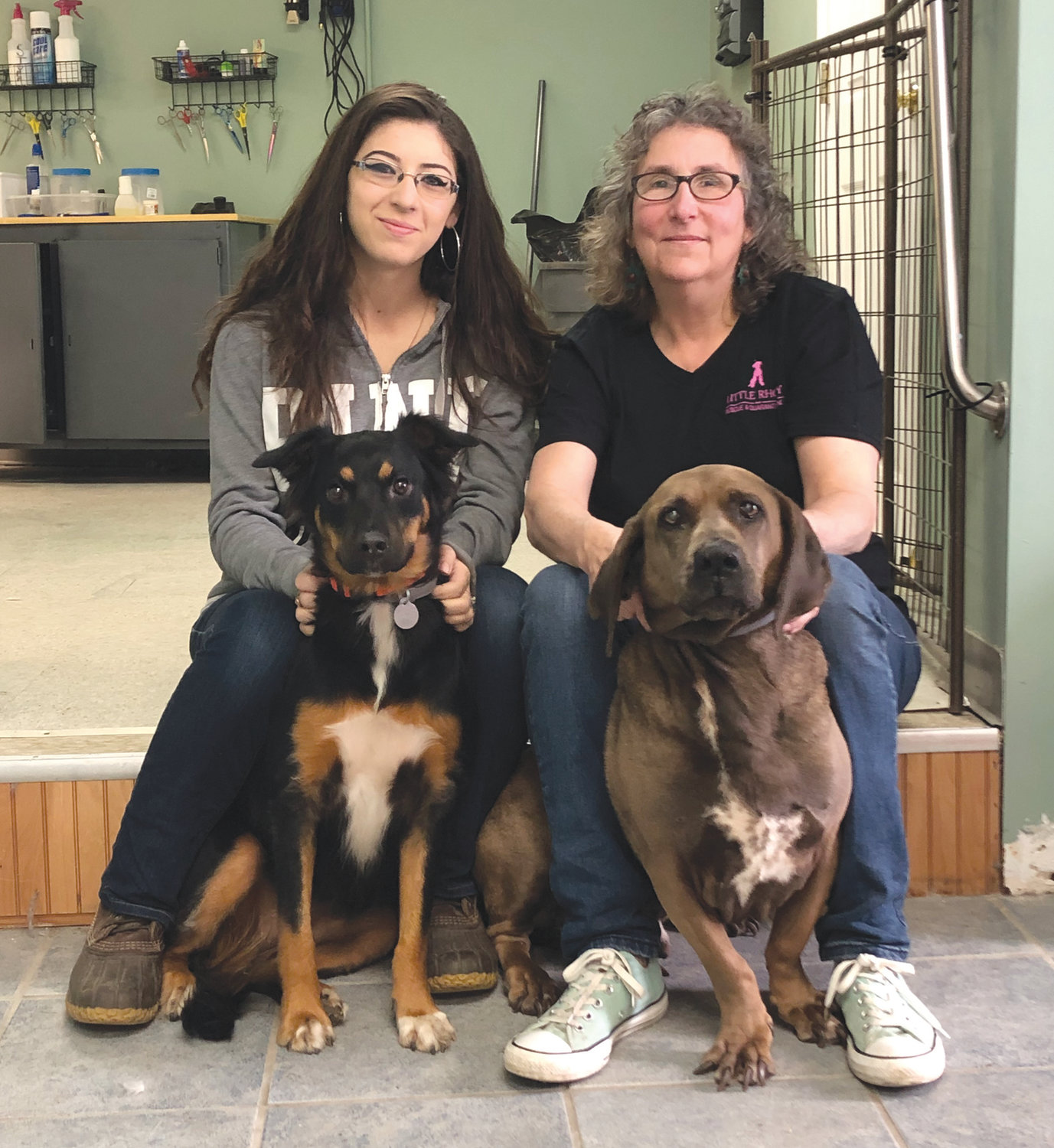 ALL HANDS (AND PAWS) ON DECK: All 4 Paws owners Mary Kathryn Kent and Jules Martins, posing here with Harley and Basset hound cross Booker, said business has been solid since opening in January.