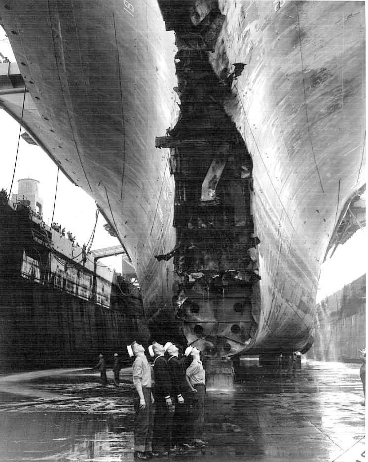 Sailors look up in wonderment at the bow of the Wasp in dry dock.