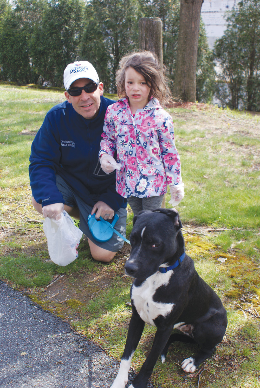 A FAMILY MATTER: Cranston Police Capt. Vin McAteer, his daughter, 3-year-old Helena, and their dog, Ranger, share a moment during the recent cleanup.